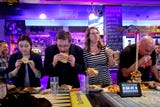 """Reporters compete against """"Max Carnage"""" during a Statesman Journal eating challenge to finish the Dark Knight Burger at Heroes Tap House in Salem."""