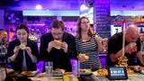 "Reporters compete against ""Max Carnage"" during a Statesman Journal eating challenge to finish the Dark Knight Burger at Heroes Tap House in Salem."