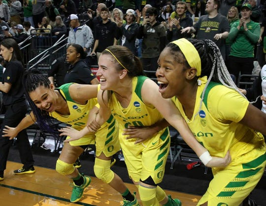 Oregon's Satou Sabally, left, Sabrina Ionescu and Ruthy Hebard, right, come off the bench in celebration of the team's 78-40 victory over Portland State in a first-round game of the NCAA women's college basketball tournament Friday, March 22, 2019, in Eugene, Ore. (AP Photo/Chris Pietsch)