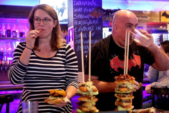 """Food and drink reporter Emily Teel, and other Statesman Journal journalists, go up against """"Max Carnage"""", a competitive eater, during an eating challenge to finish the Dark Knight Burger, consisting of six top-selling burgers, at Heroes Tap House in Salem on March 22, 2019. The Statesman Journal crew finished the stack in 35 minutes."""