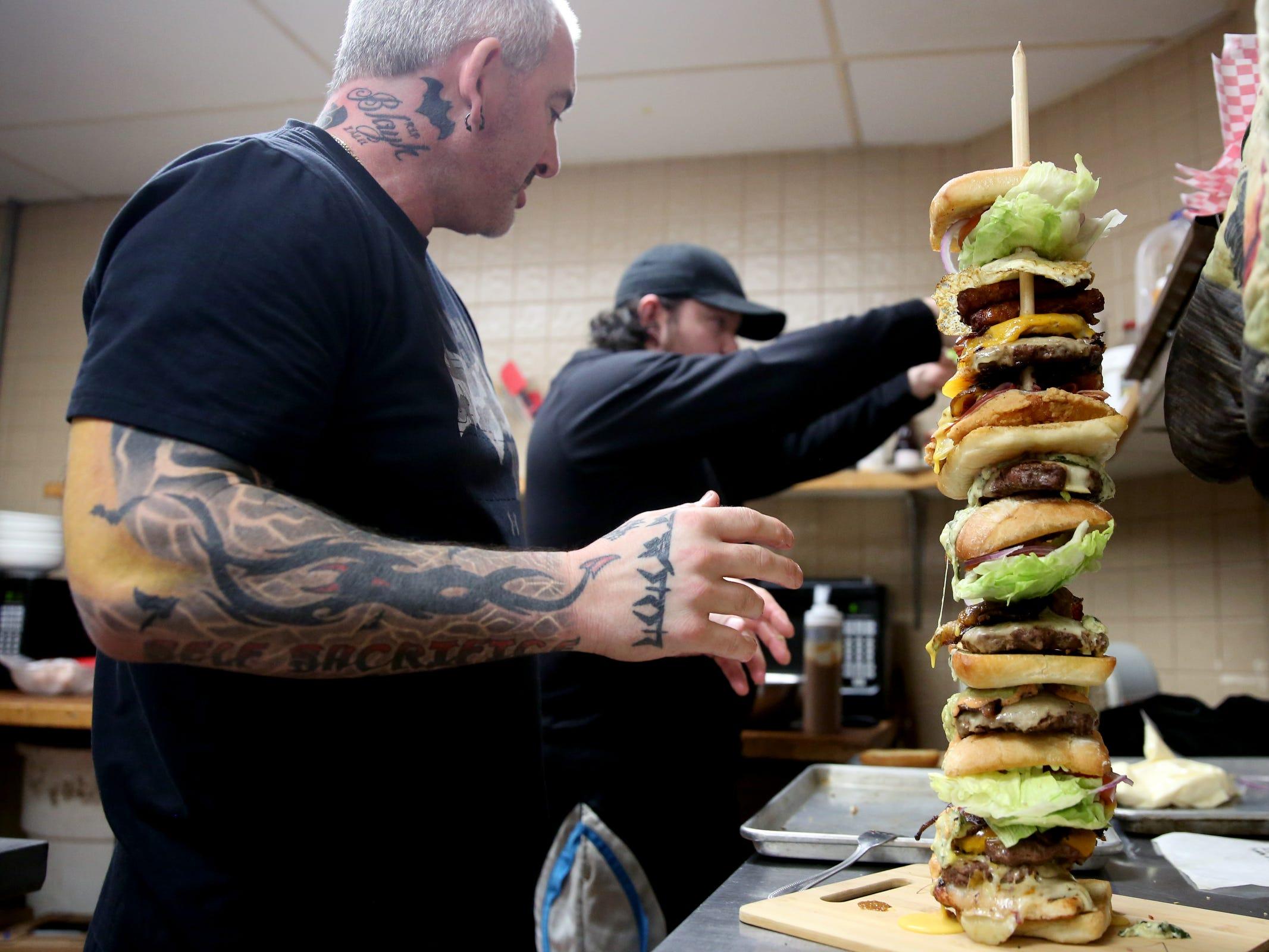 "Donovan Wallace, a Heroes Tap House owner, assembles the food for a Statesman Journal eating challenge against professional competitive eater ""Max Carnage"" to finish the Dark Knight Burger, consisting of six top-selling burgers, at Heroes Tap House in Salem on March 22, 2019. The Statesman Journal crew finished the stack in 35 minutes."