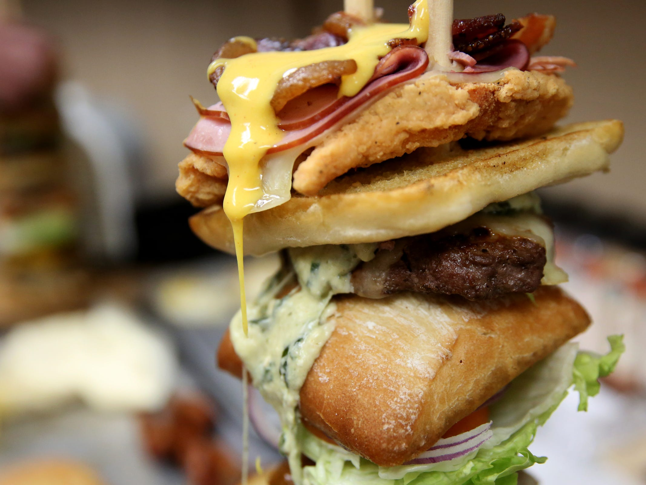 "The burgers are stacked for a Statesman Journal eating challenge against professional competitive eater ""Max Carnage"" to finish the Dark Knight Burger, consisting of six top-selling burgers, at Heroes Tap House in Salem on March 22, 2019. The Statesman Journal crew finished the stack in 35 minutes."