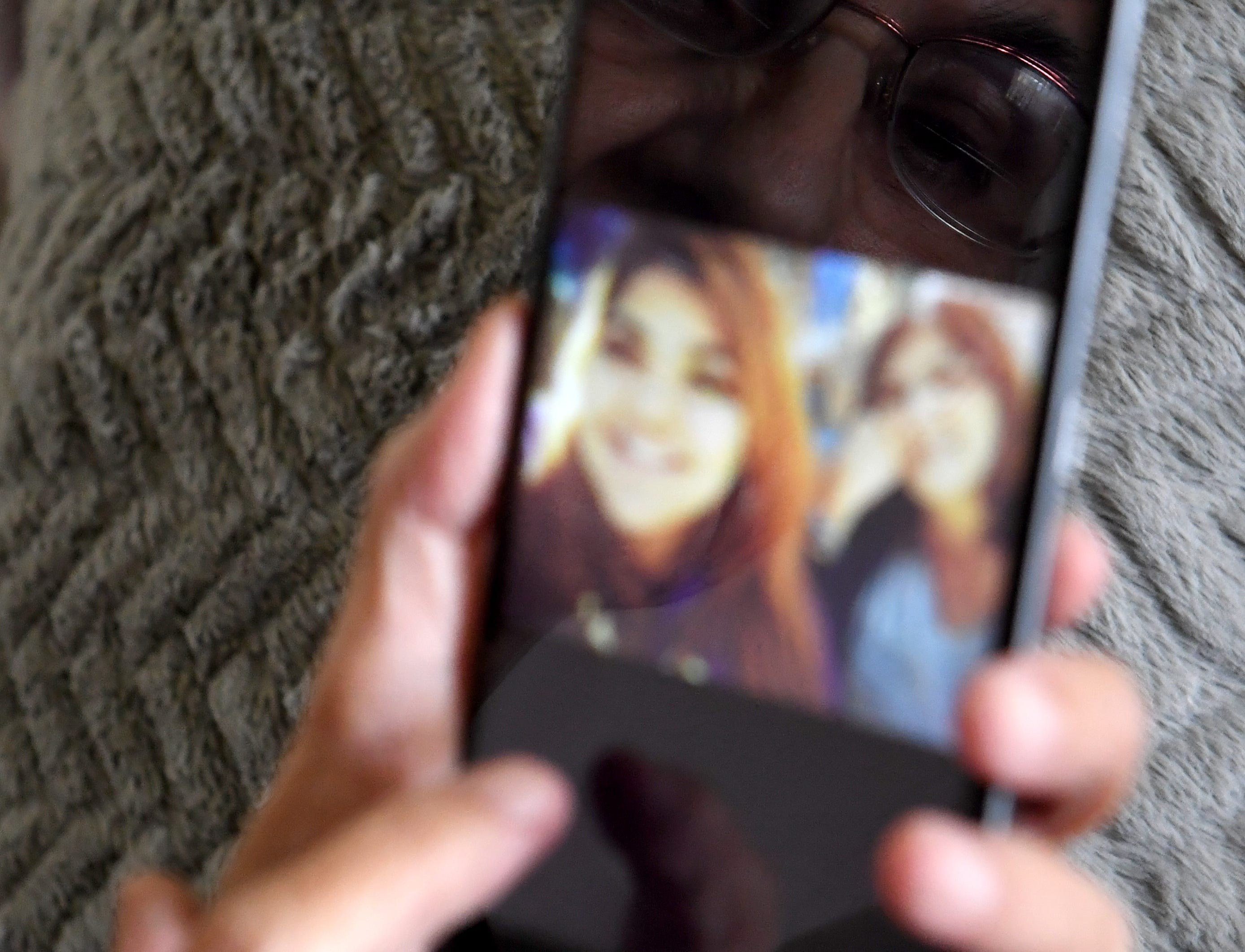 Gloria Torrez looks through photos of happier times on her phone.