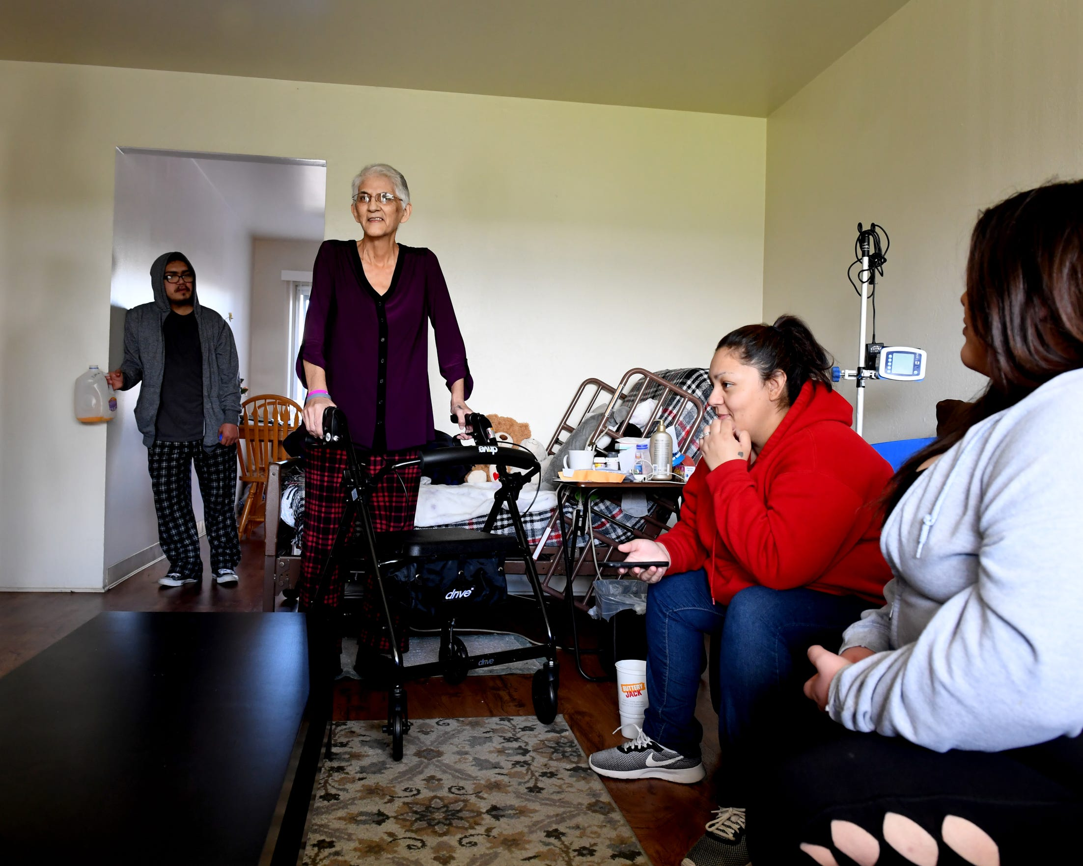 Gloria Torrez (standing) speaks with her family at her Salinas home in March 2019.