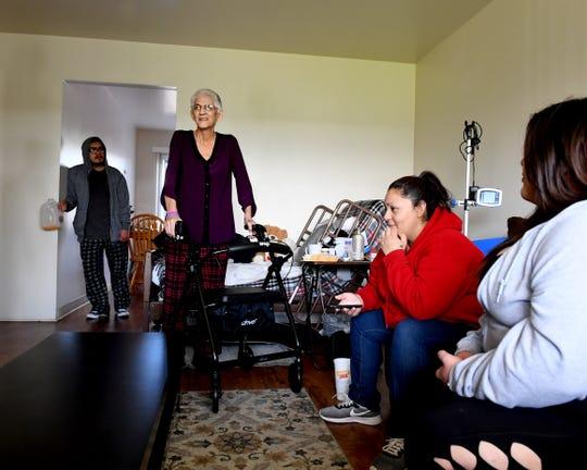 Gloria Torrez (de pie) habla con su familia en su hogar en Salinas en marzo de 2019.