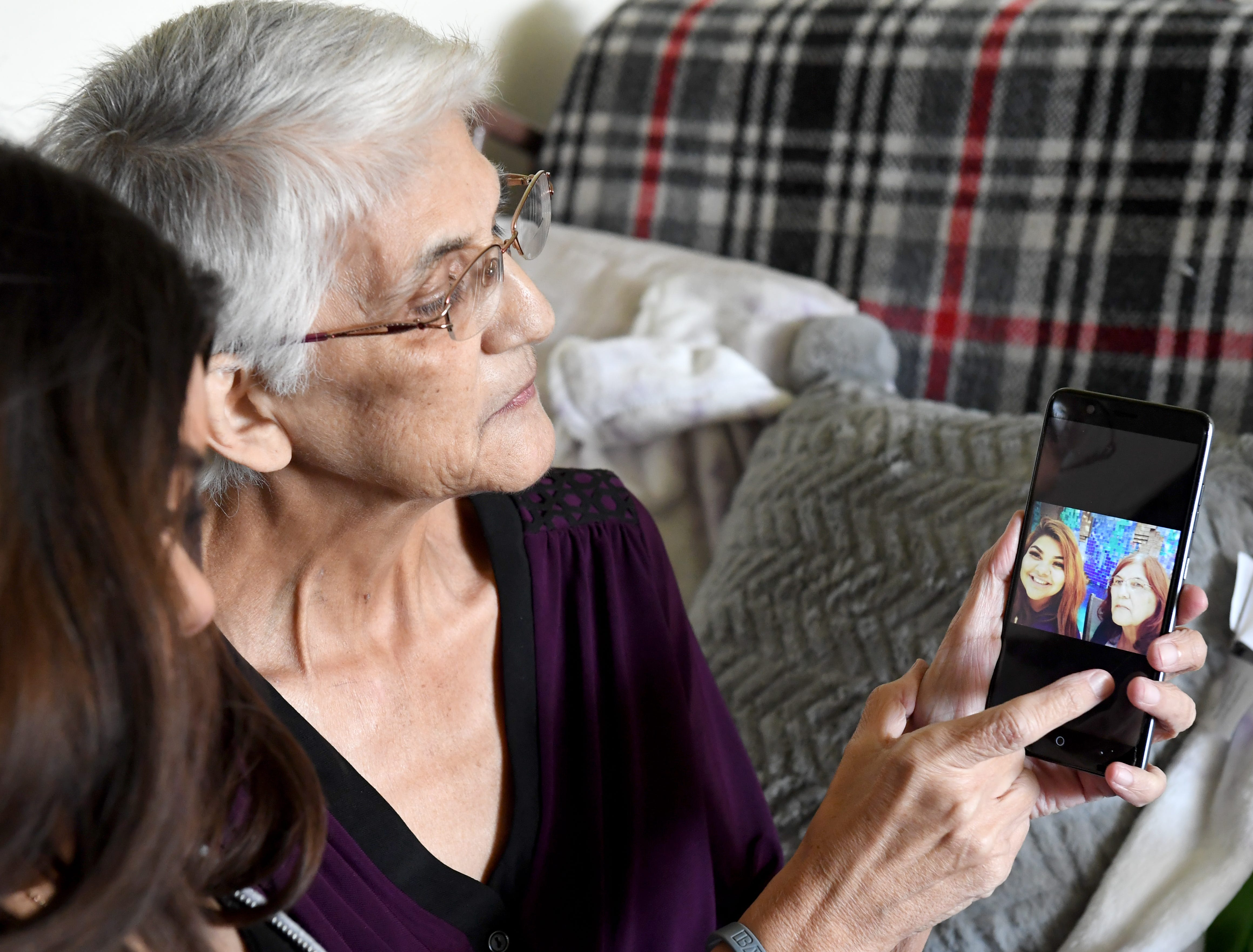 Gloria Torrez scrolls through photos from happier times on her phone.