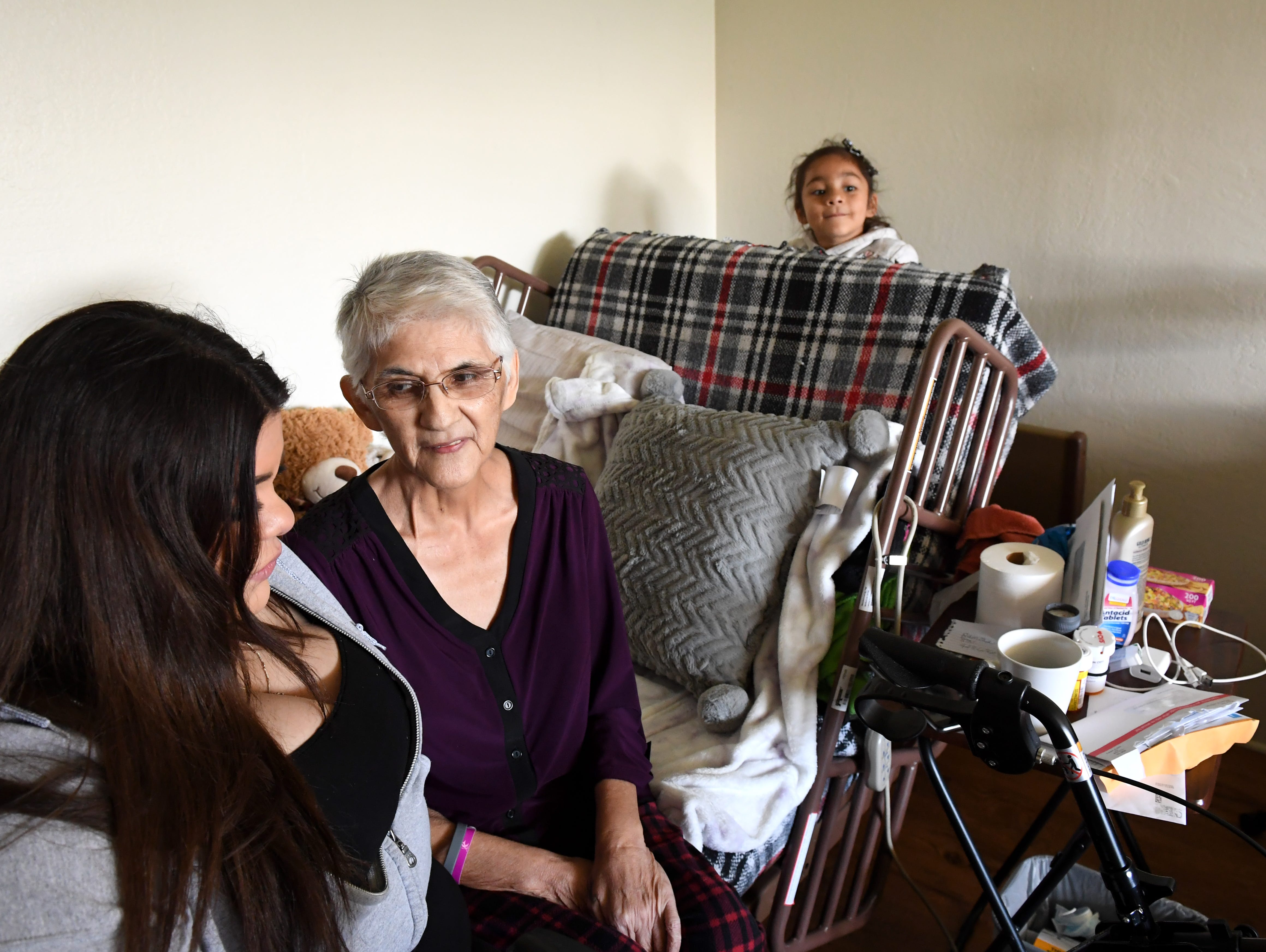 Gloria Torrez (middle seated) speaks with her granddaughter Gloria (left seated) while her other granddaughter Tiana plays behind her bed.