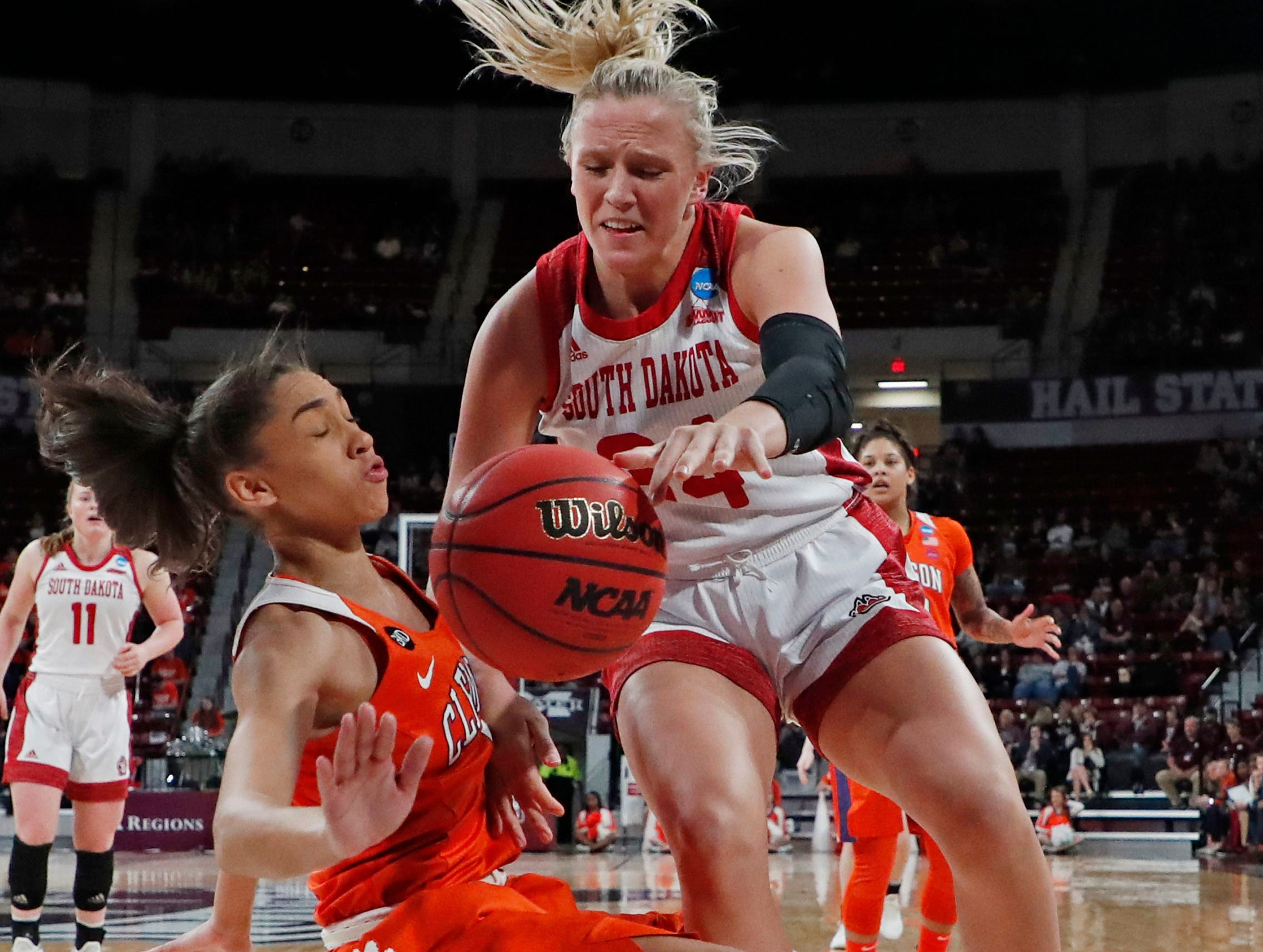 South Dakota center Hannah Sjerven (34) crashes into Clemson guard Danielle Edwards, left, while trying to dribble past in the NCAA Tournament in Starkville, Miss., Friday, March 22, 2019. (AP Photo/Rogelio V. Solis)