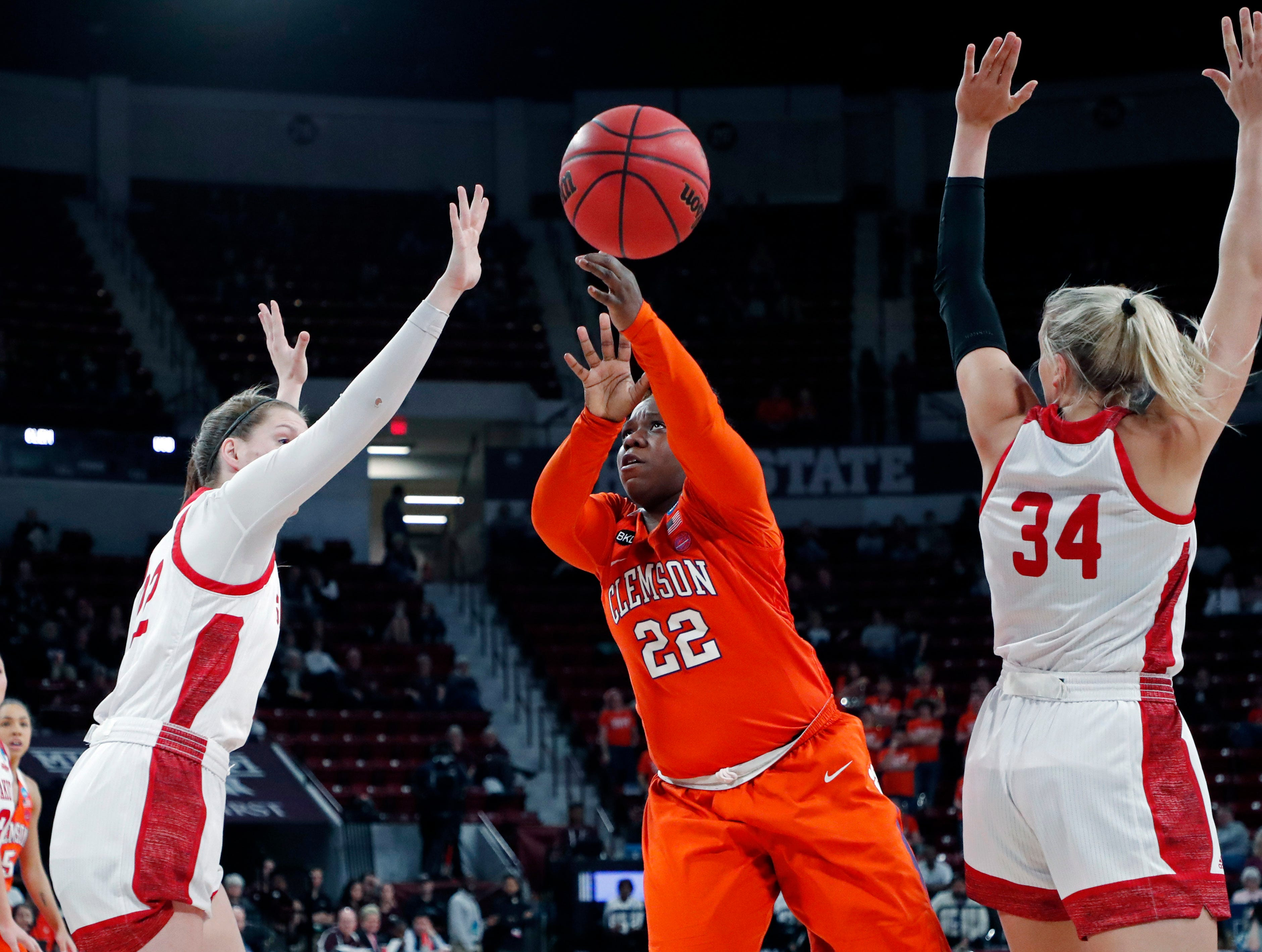 Clemson guard Keniece Purvis (22) attempts a shot between South Dakota guard Chloe Lamb (22) and center Hannah Sjerven (34) during a first round women's college basketball game in the NCAA Tournament in Starkville, Miss., Friday, March 22, 2019. (AP Photo/Rogelio V. Solis)