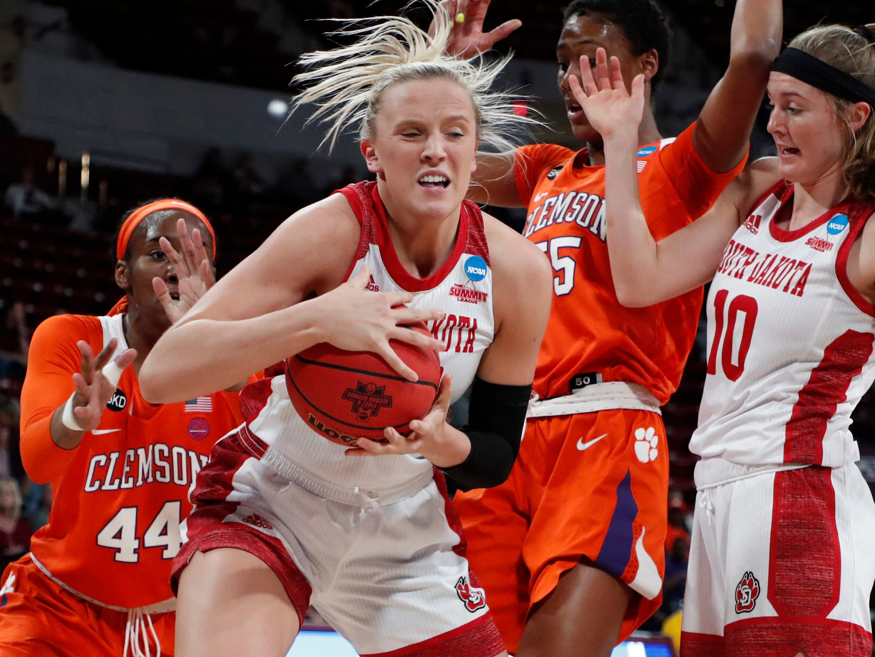 South Dakota center Hannah Sjerven, second from left, pulls down a rebound in front of Clemson center Kobi Thornton (44) and forward Tylar Bennett (55) during a first round women's college basketball game in the NCAA Tournament in Starkville, Miss., Friday, March 22, 2019. (AP Photo/Rogelio V. Solis)