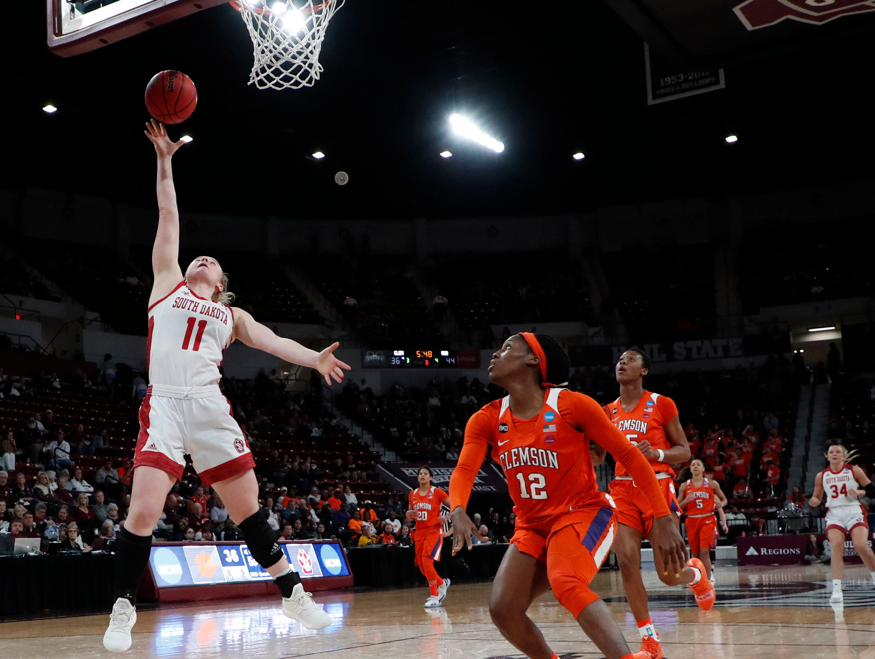 South Dakota guard Monica Arens (11) shoots a layup while Clemson guard Aliyah Collier (12) attempts to defend during the second half of a first round women's college basketball game in the NCAA Tournament in Starkville, Miss., Friday, March 22, 2019. (AP Photo/Rogelio V. Solis)