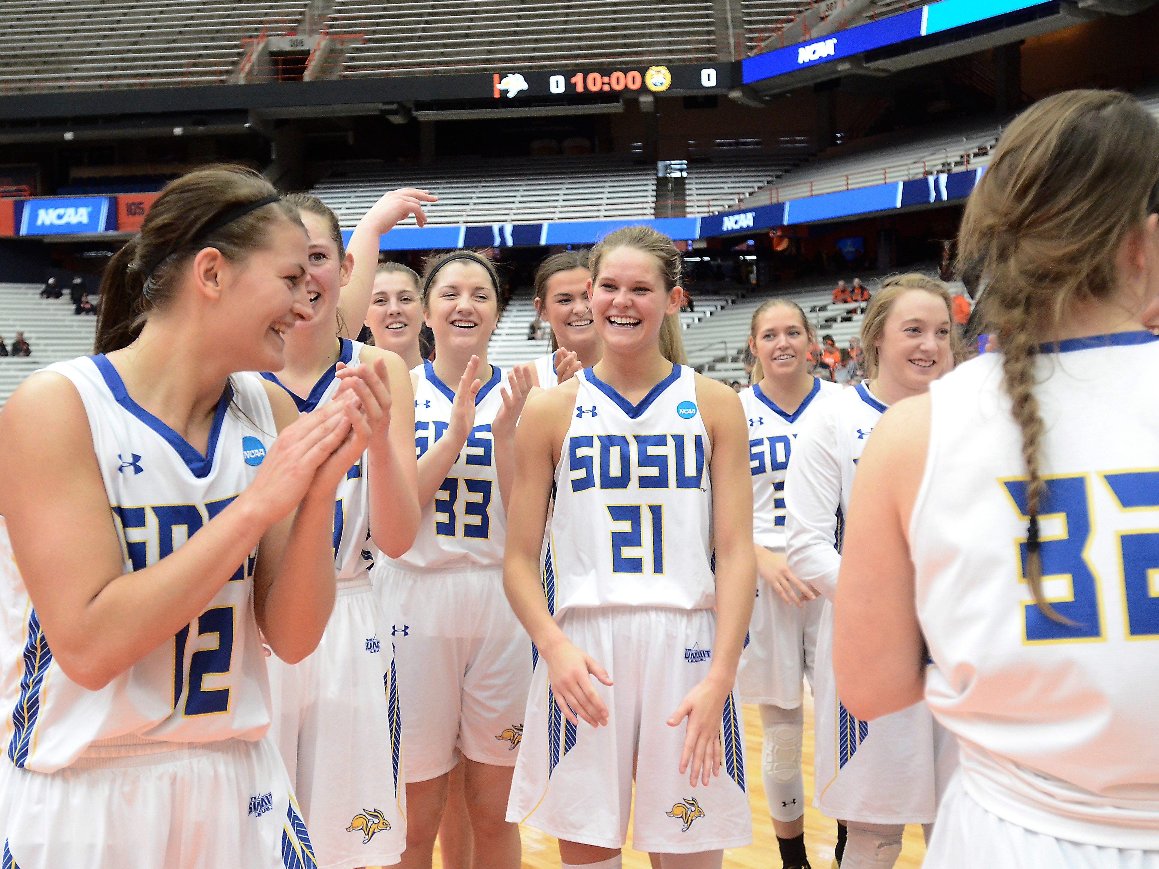 South Dakota State players celebrate after they defeated Quinnipiac in a first-round game in the NCAA women's college basketball tournament in Syracuse, N.Y., Saturday, March 23, 2019. (AP Photo/Heather Ainsworth)