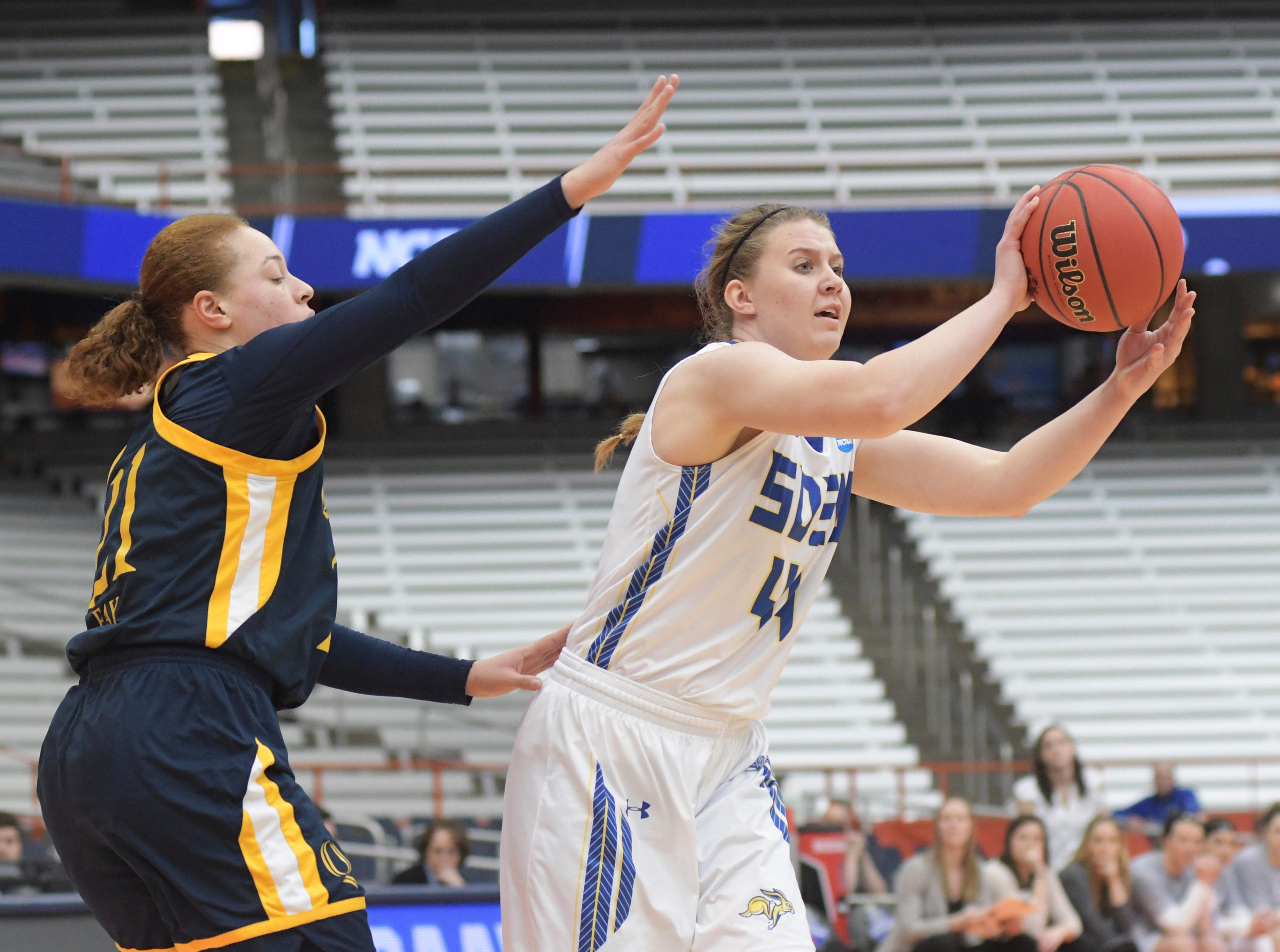 South Dakota State's Myah Selland (44) passes the ball away from Quinnipiac's Jen Fay during of a first-round game in the NCAA women's college basketball tournament in Syracuse, N.Y., Saturday, March 23, 2019. South Dakota State won 76-65. (AP Photo/Heather Ainsworth)