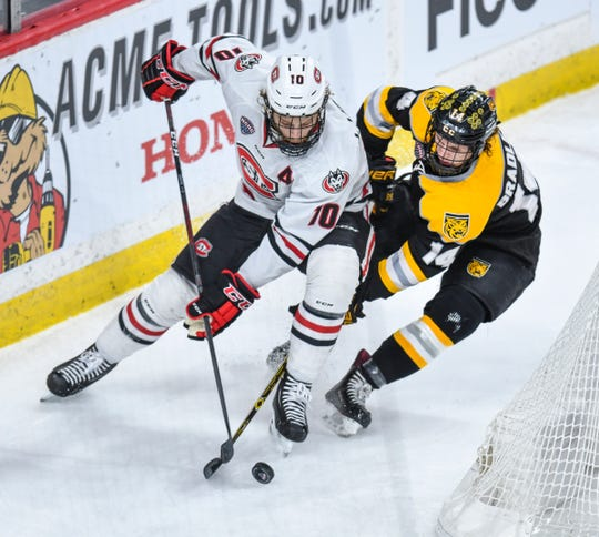 St. Cloud State's Jon Lizotte skates along the boards while being chased by Trey Bradley of Colorado College during the NCHC Frozen Faceoff semifinals Friday, March 22, at the Xcel Energy Center in St. Paul.