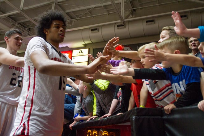 Harrison Butler high fives T-Bird fans after the team's CIT win over Drake last week. Butler played almost 26 minutes per game as a freshman this season.