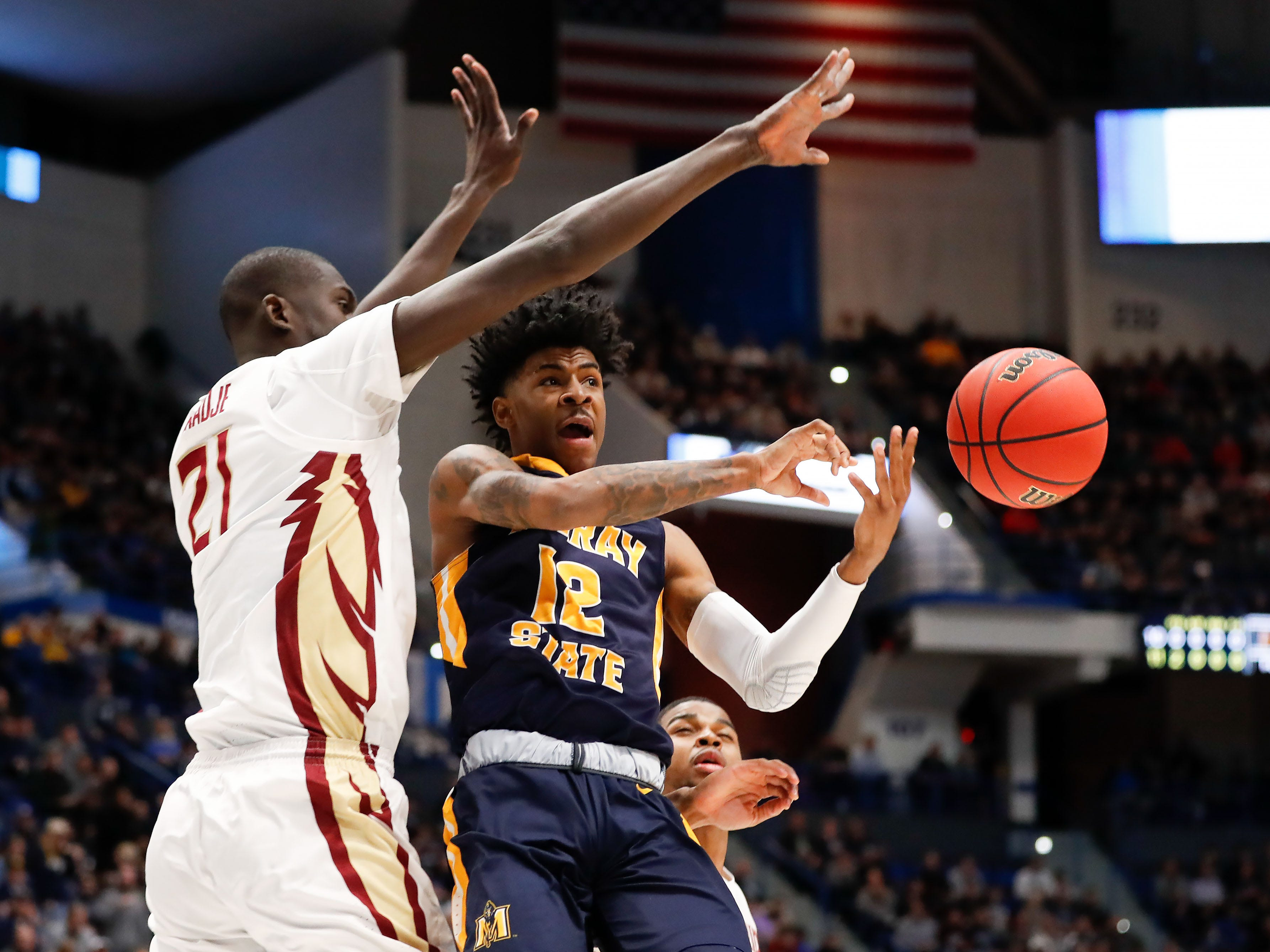 Mar 23, 2019; Hartford, CT, USA; Murray State Racers guard Ja Morant (12) passes the ball around Florida State Seminoles center Christ Koumadje (21) during the first half of a game in the second round of the 2019 NCAA Tournament at XL Center. Mandatory Credit: David Butler II-USA TODAY Sports