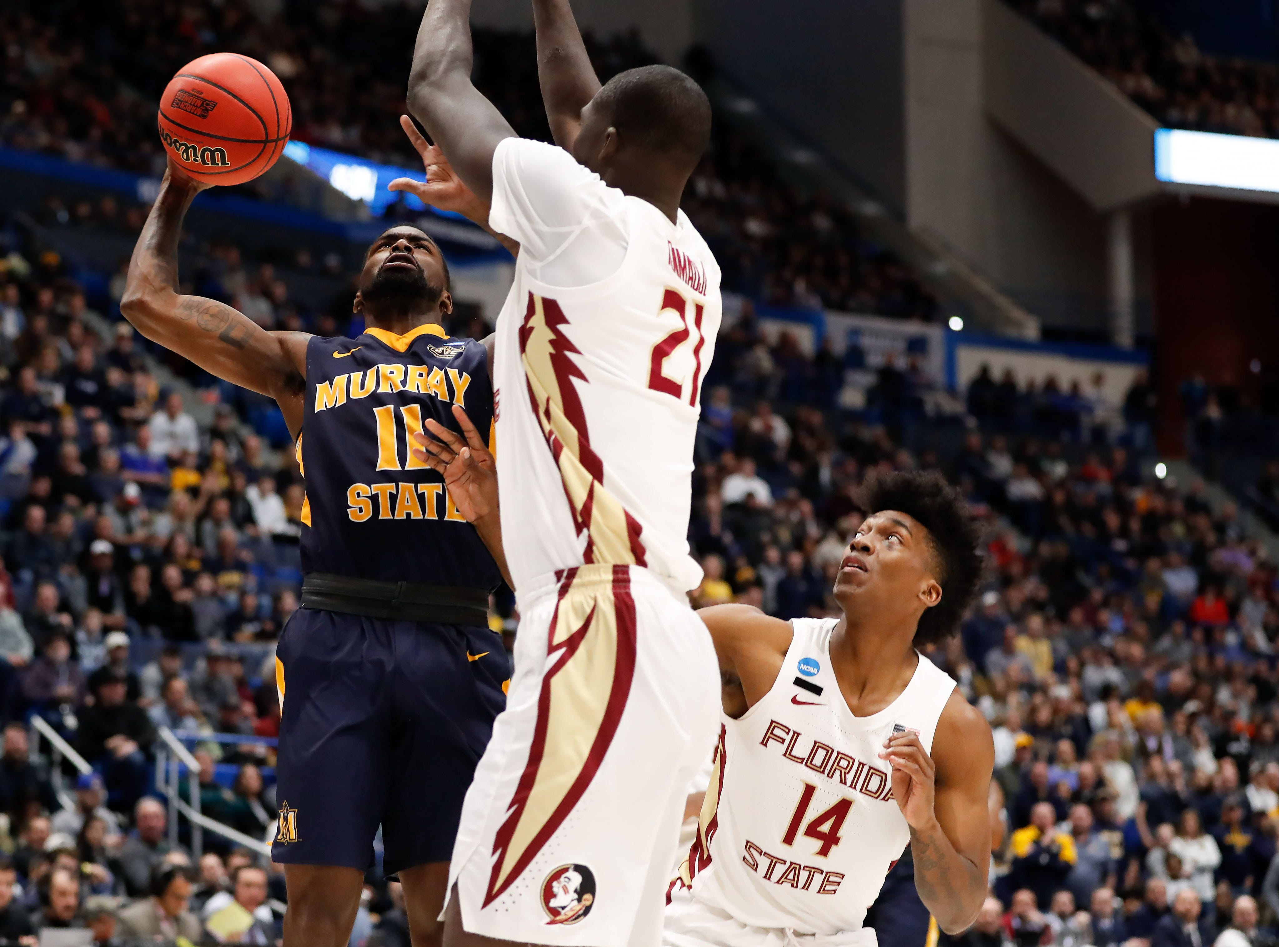 Mar 23, 2019; Hartford, CT, USA; Murray State Racers guard Shaq Buchanan (11) attempts a layup against Florida State Seminoles center Christ Koumadje (21) and guard Terance Mann (14) during the first half of a game in the second round of the 2019 NCAA Tournament at XL Center. Mandatory Credit: David Butler II-USA TODAY Sports