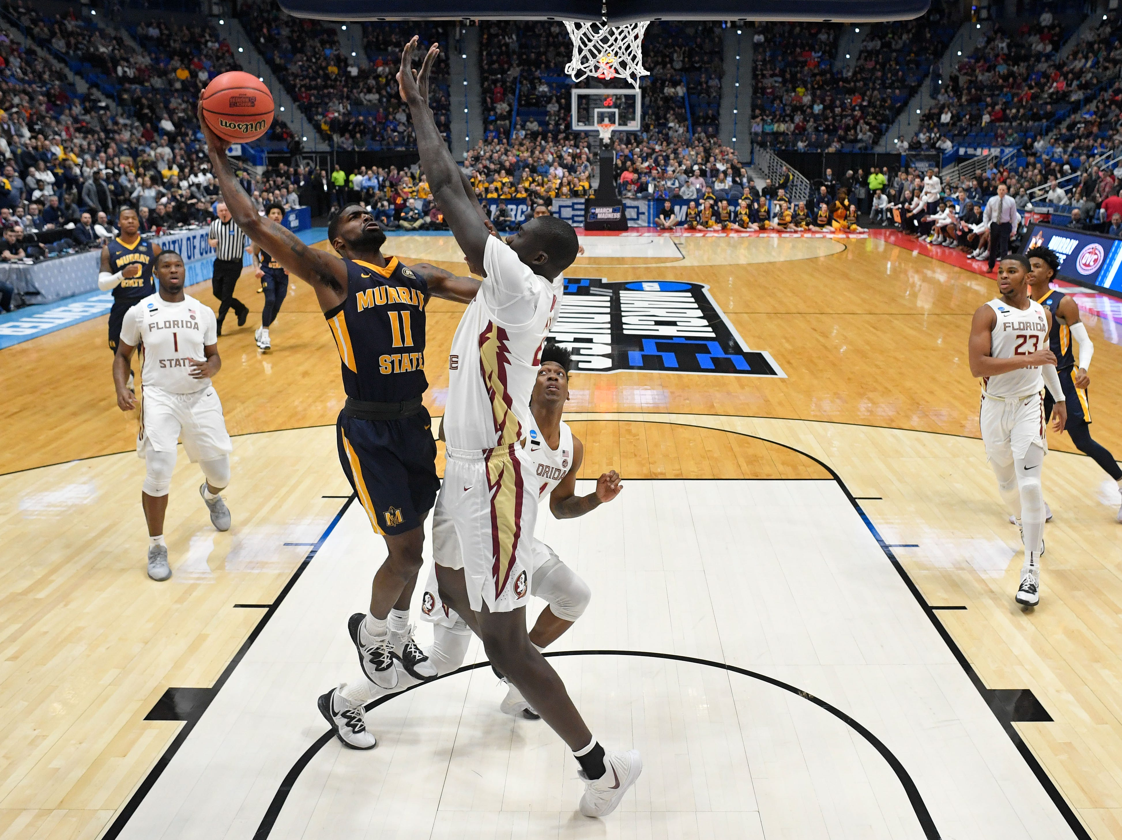 Mar 23, 2019; Hartford, CT, USA; Murray State Racers guard Shaq Buchanan (11) attempts a layup against Florida State Seminoles center Christ Koumadje (21) during the first half of a game in the second round of the 2019 NCAA Tournament at XL Center. Mandatory Credit: David Butler II-USA TODAY Sports