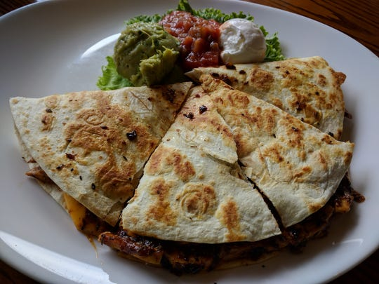 Mo-Bay Grill's jerk chicken quesadilla features perfectly spiced sweet and spicy sliced chicken breast and cheddar cheese melted in the quesadilla and served with salsa, guacamole and sour cream.
