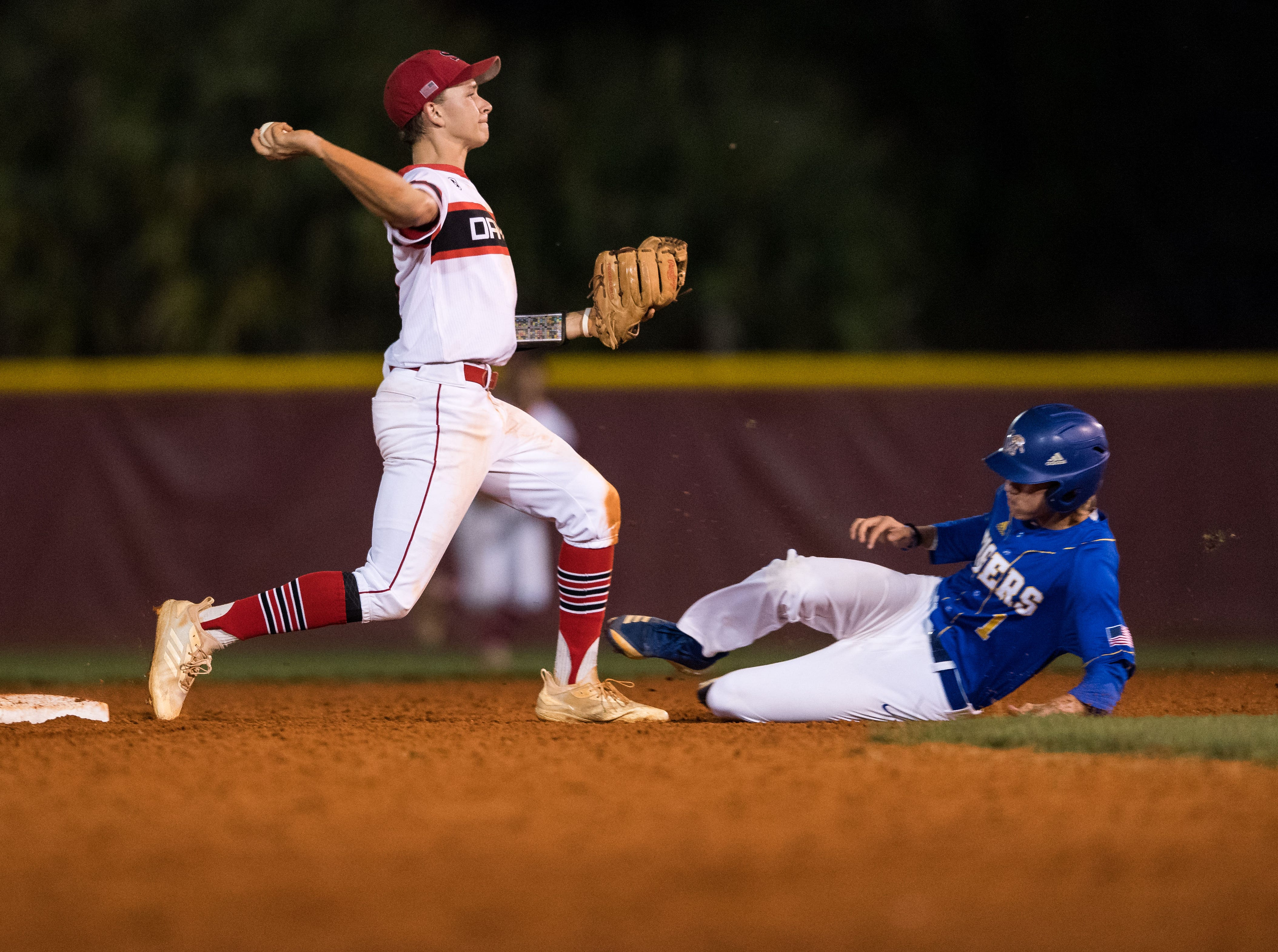 South Fork second-baseman Tim Kudlinski (left) throws to first after forcing Martin County's Damon Blinde out at second, making a double play due to an interference call, to end the top of the fifth inning at the 2019 Robbie Souza Classic high school baseball game Friday, March 22, 2019, at South Fork High School in Tropical Farms. Martin County won, 5-1.
