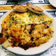 The Gyro omelet with added spinach shown with home fries and an English muffin.