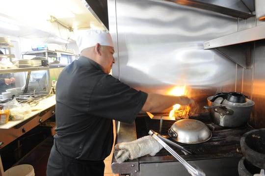 Arturo Cruz, chef at DV's Mexican Grill in Ventura, cooks salmon at the new restaurant at 3845 Telegraph Road, Ventura.