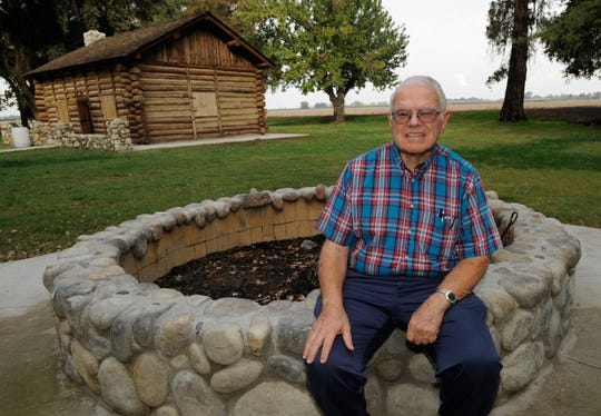 Boy Scout leader Bob Ludekens sits on the firepit built as an Eagle Scout project by Kristopher Perry. T