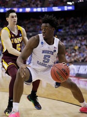 North Carolina's Nassir Little, right, drives past Iona's Ben Perez in the first half during a first round men's college basketball game in the NCAA Tournament in Columbus, Ohio, Friday, March 22, 2019. (AP Photo/Tony Dejak)
