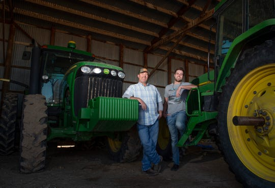 """In this Friday, March 15, 2019 photo, Grant Cummins and his son Parker have their photo taken with some of the tractors they use to farm mint near Murtaugh, Idaho. Extracting oil from the peppermint crop is only part of Cummins' business. Cummins, Chad Neeley, president of the Idaho Mint Growers Association said, is one mint grower who has gone """"all in"""" by growing and selling certified rootstock in addition to producing oil."""