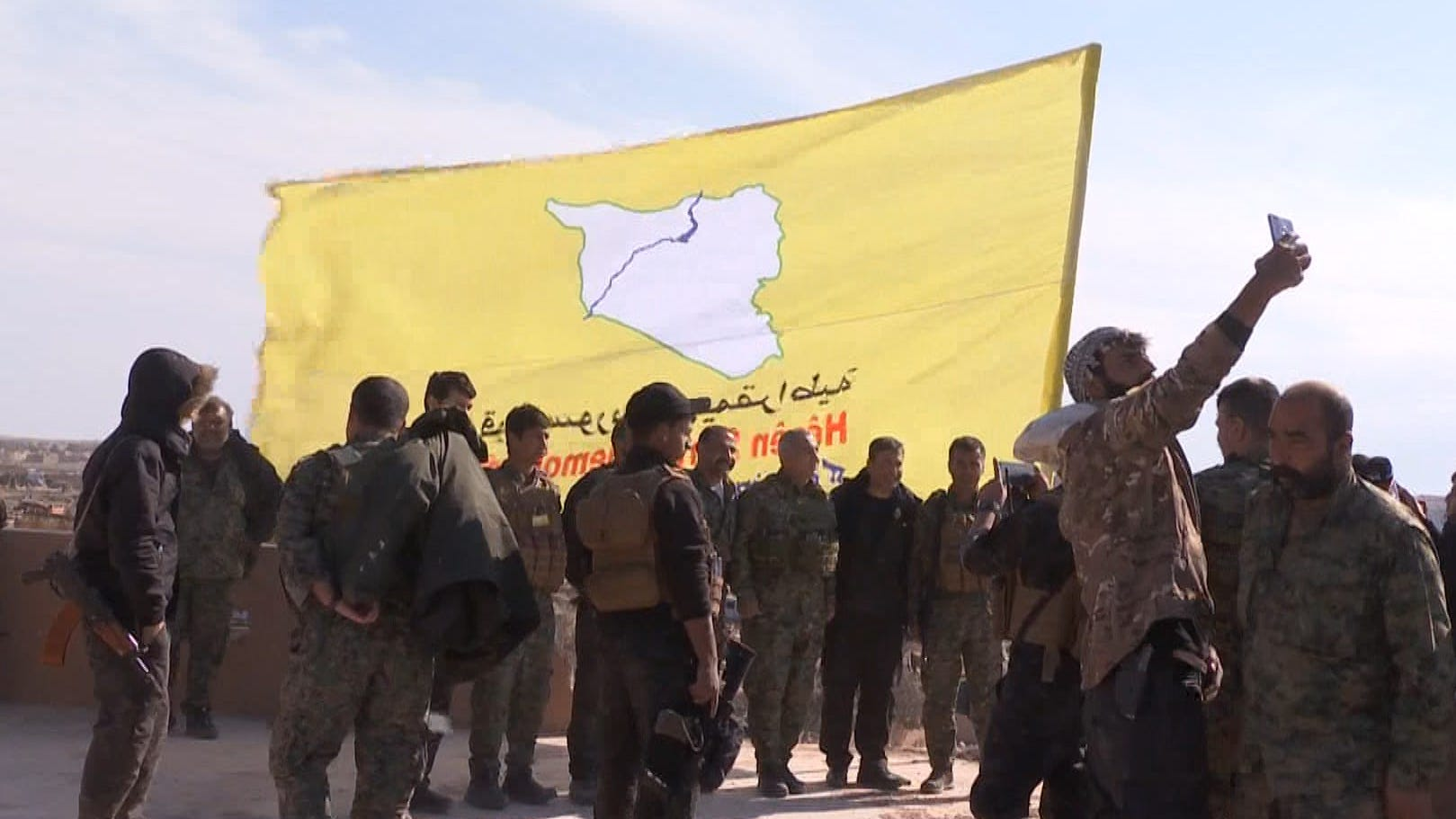 An image grab released by the Kurdish Ronahi TV on March 23, 2019 shows the US-backed Syrian Democratic Forces (SDF) raising their flag atop a building in the Islamic State group's bastion in the eastern Syrian village of Baghouz.