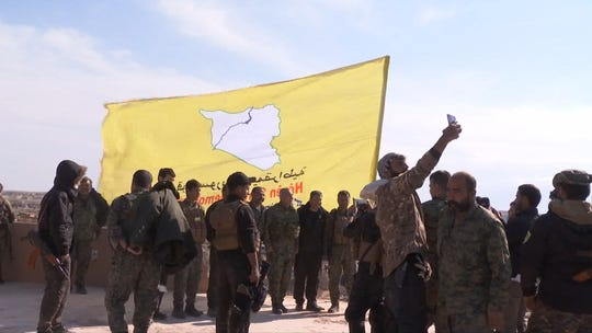 An image grab released by the Kurdish Ronahi TV on March 23, 2019, shows the US-backed Syrian Democratic Forces (SDF) raising their flag atop a building in the Islamic State group's bastion in the eastern Syrian village of Baghouz.