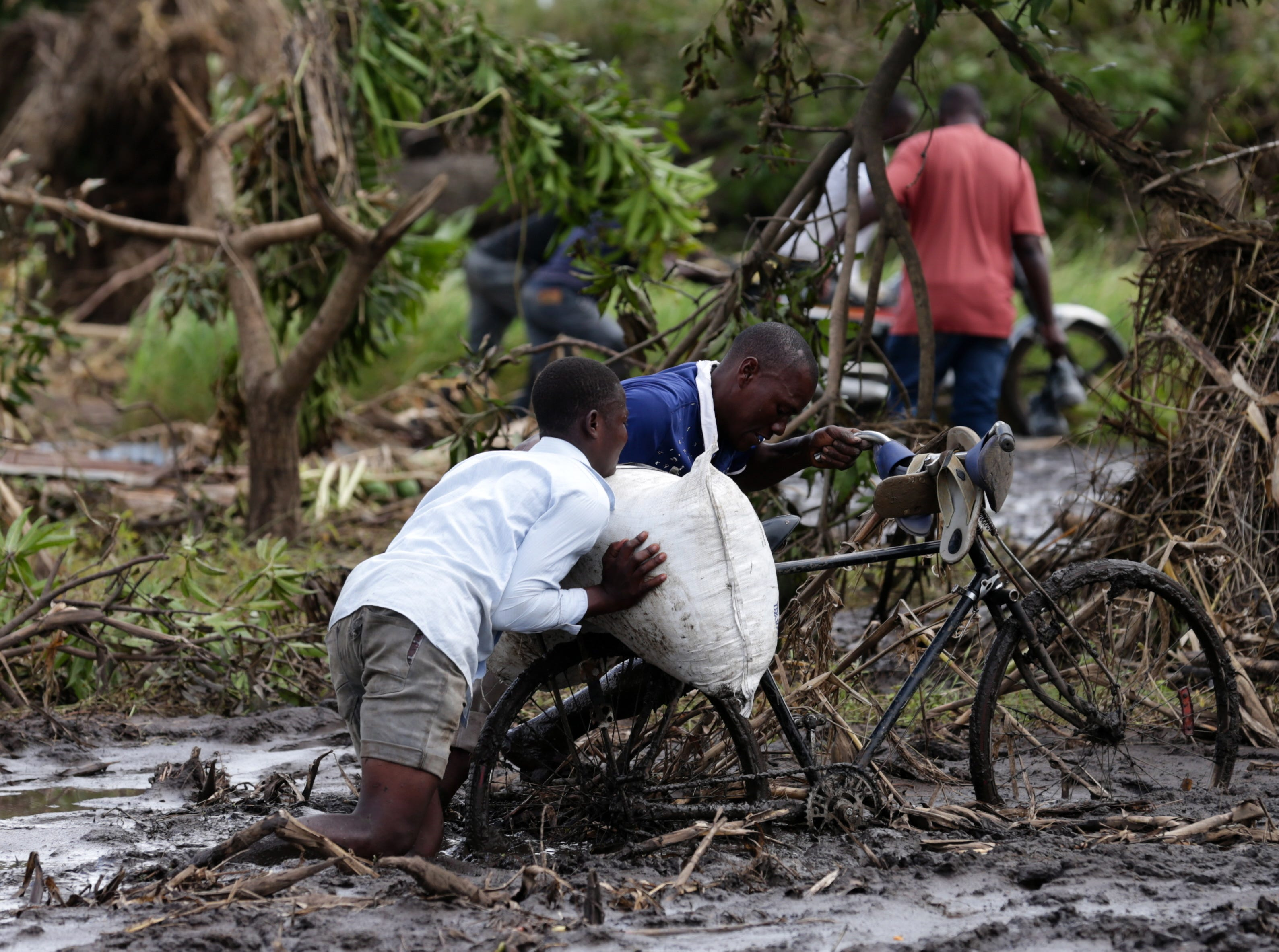 Two men push a bicycle through mud on the only access route possible in the area of Joao Segredo where the national road 6 was interrupted after the passage of cyclone Idai in the province of Sofala, central Mozambique on March 23, 2019.  The National Disasters Management Institute of Mozambique said 417 people lost their lives by Cyclone Idai, 301 of them died in the central province of Sofala, where 123 people died in the badly hit regional capital Beira.