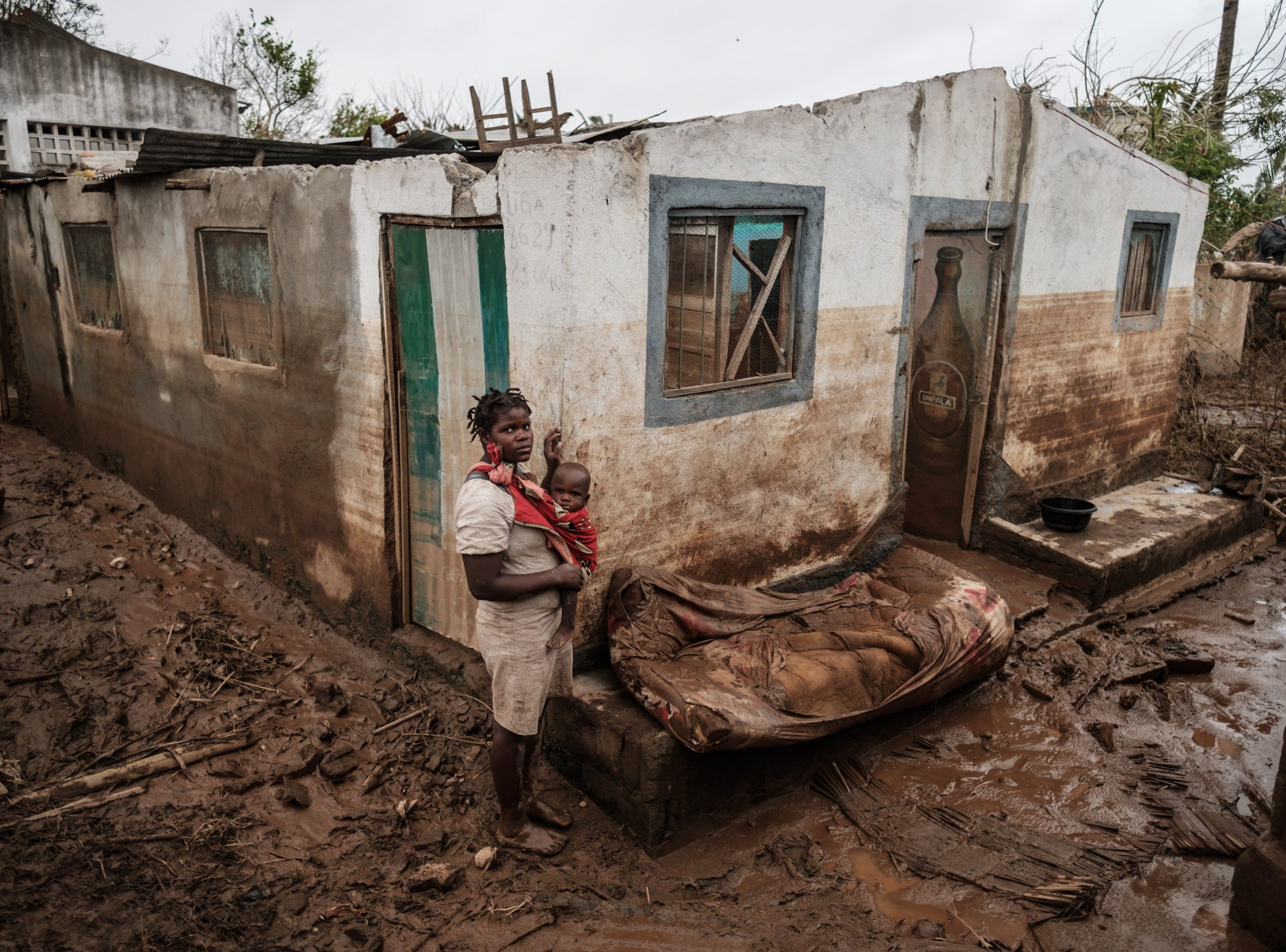 Rosa Tomas, 27, poses with her one-year-old son Dionisio Eduardo, in front of their destroyed and mud-covered home in Buzi, Mozambique, on March 23, 2019, after the area was hit by the Cyclone Idai.