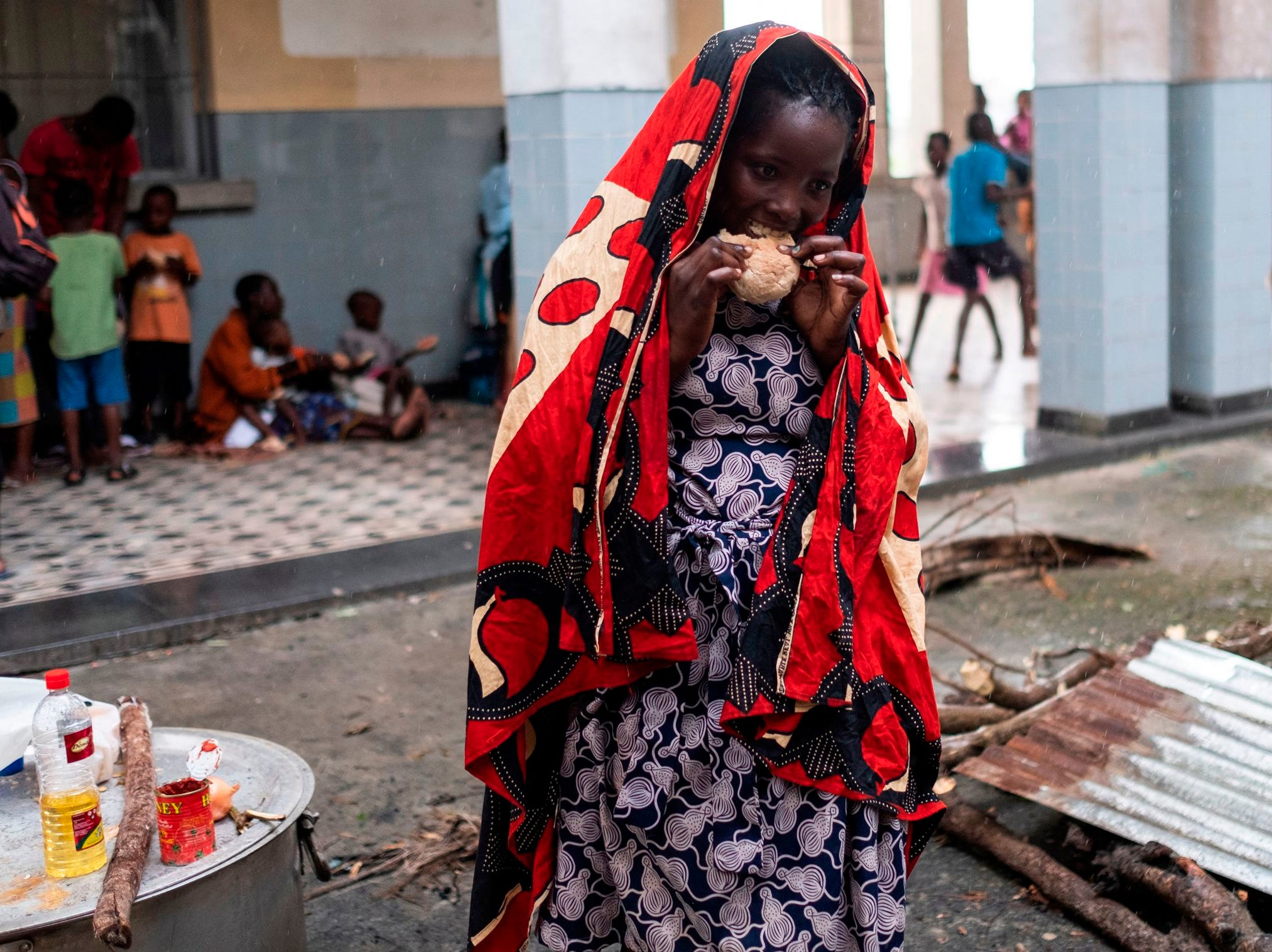 A woman with a scarf on her head to protect her from the rain, eats bread that has been given to displaced people at the Samora Machel High School in Beira, Mozambique, on March 23, 2019.