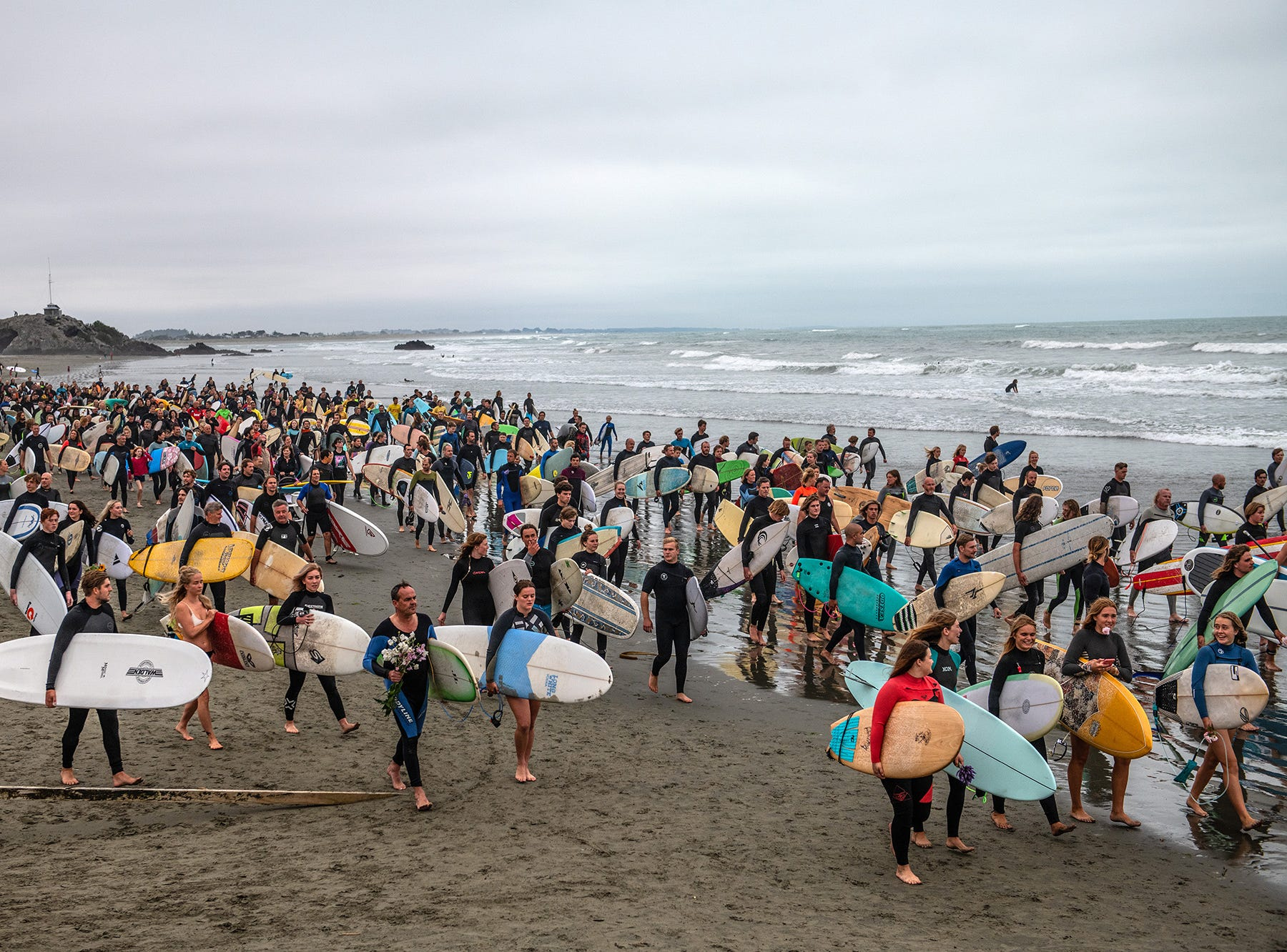 Surfers carry their boards as they walk along a beach before forming a circle at sea to remember victims of the Christchurch mosque attacks, on March 23, 2019 in Christchurch, New Zealand.