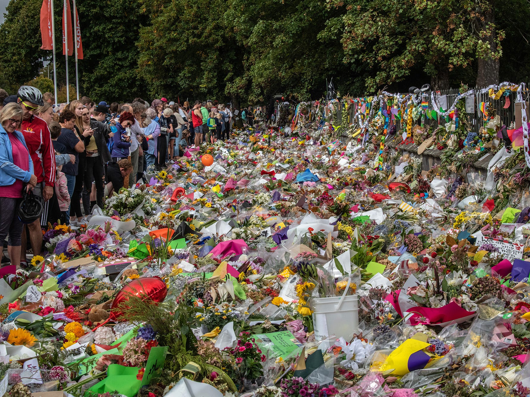 People view flowers and tributes as others nearby take part in a march to remember victims of the Christchurch mosque attacks, on March 23, 2019 in Christchurch, New Zealand.