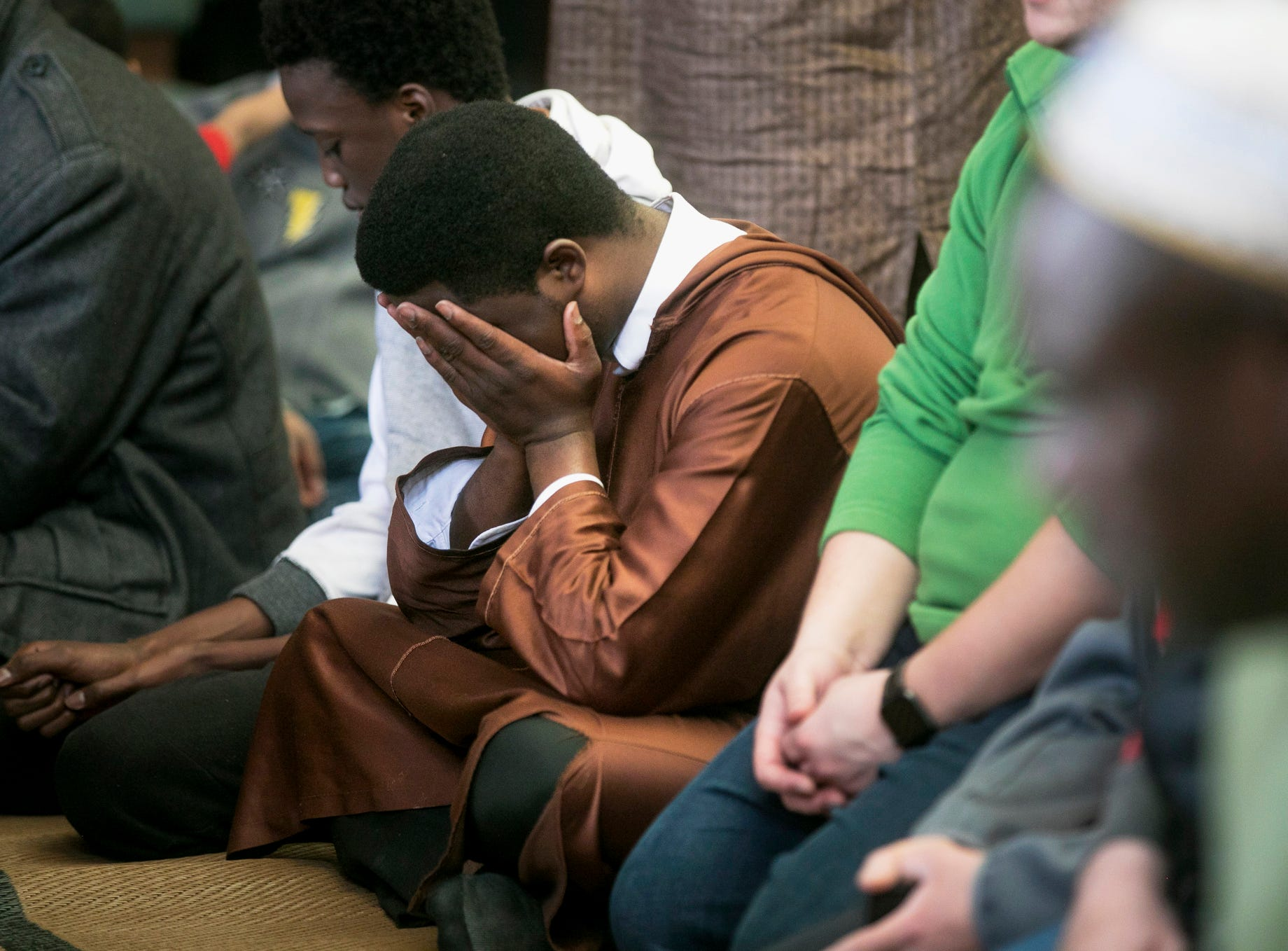 Saidoa Ly covers his face in a prayer for the New Zealand mosque shooting victims during an event held by the Summit Colorado Interfaith Council Friday, March 22, 2019, at the Lord of the Mountains Church in Dillon, Colo.