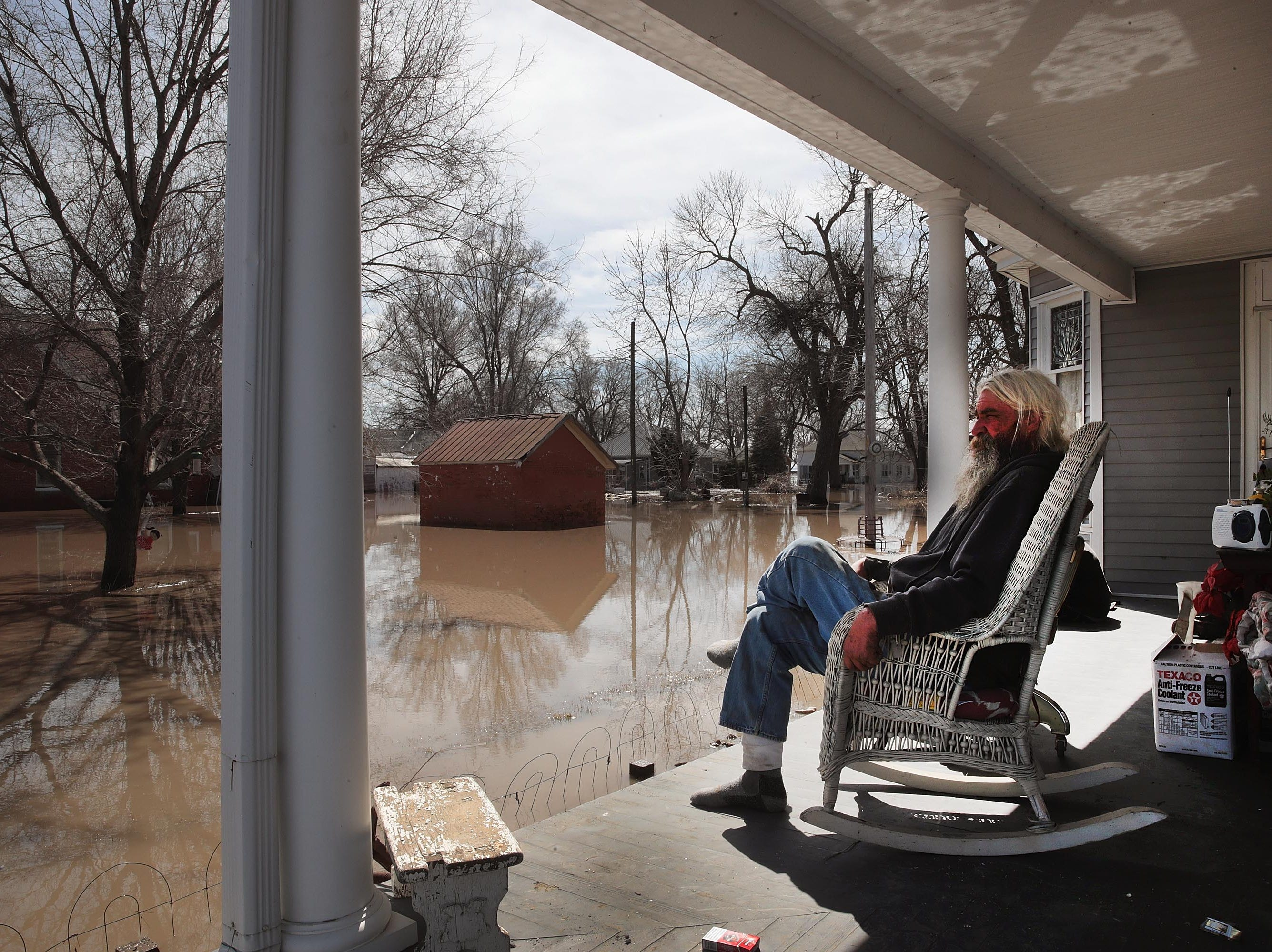 Mike Rasnic sits on the front porch of his home which is surrounded by floodwater on March 22, 2019 in Craig, Mo.