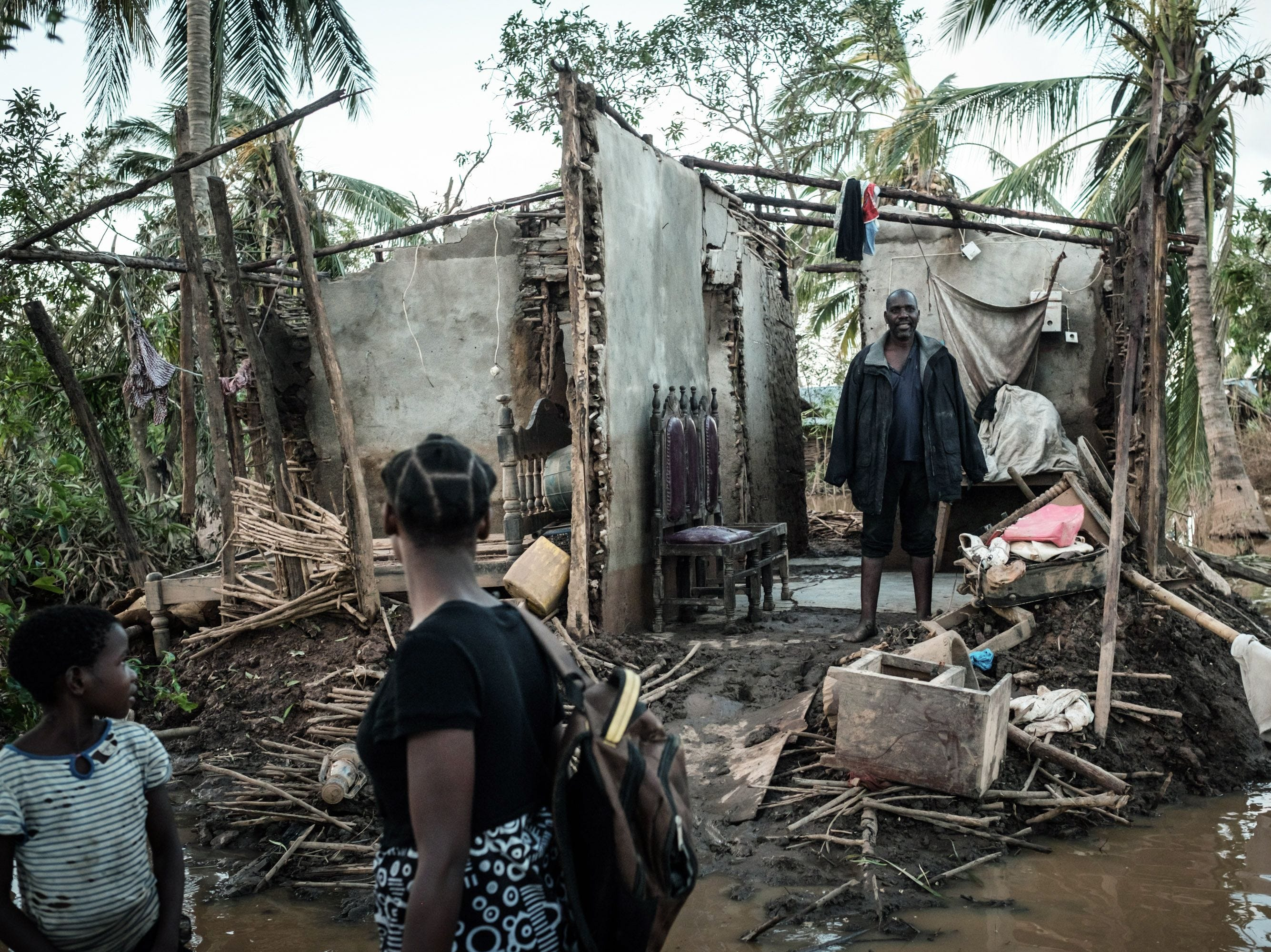 Rosita Moises Zacarias, center, 15, and her sister Joaninha Manuel, left, 9, look at their father Francisco Simon in their house destroyed by the cyclone Idai as they go to seep in a shelter in Buzi, Mozambique, on March 22, 2019.