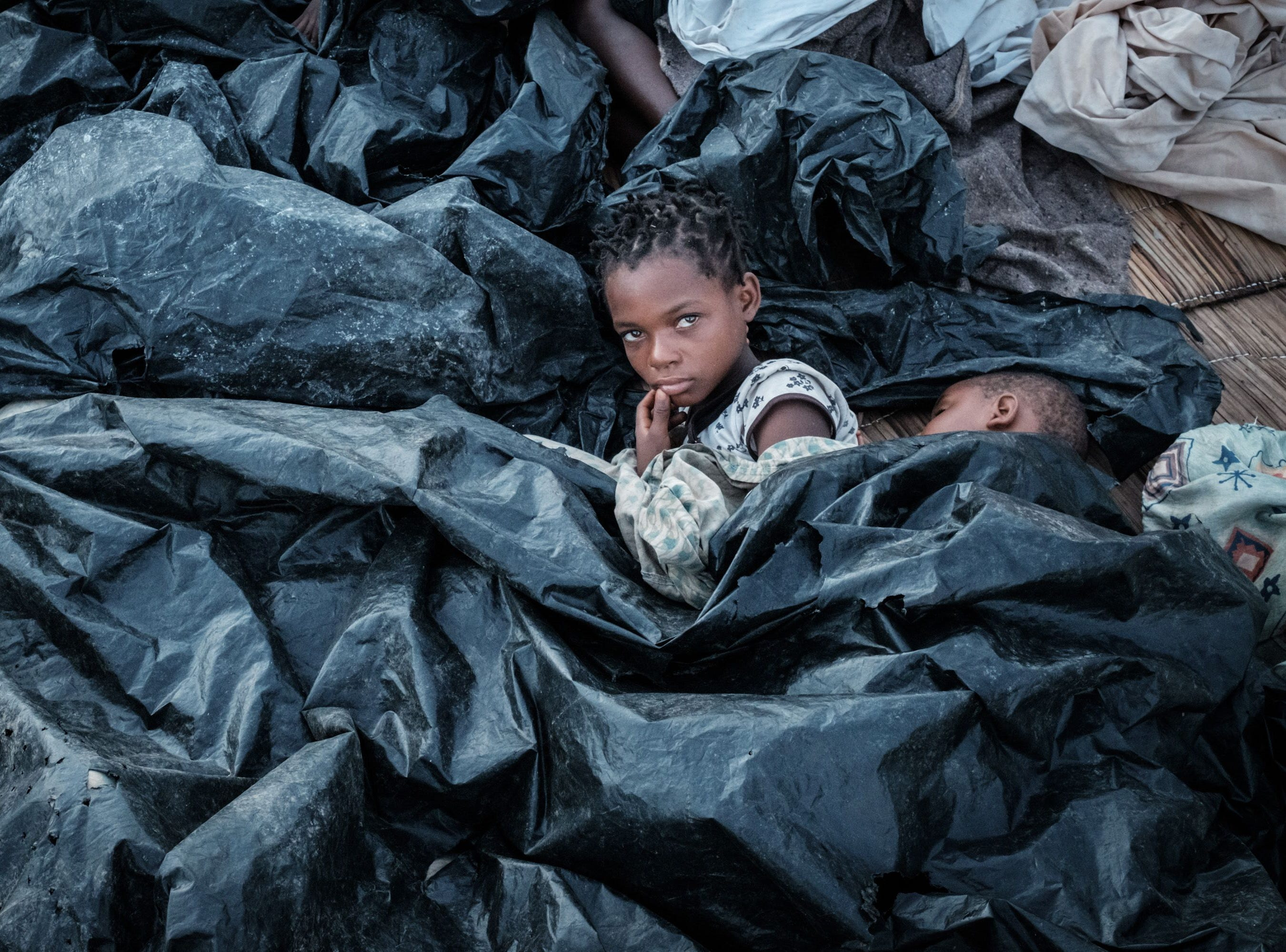 Enia Joaquin Luis, 11, wakes up beside her sister Luisa, 6, under plastic sheets for protect themselves from rain as they stay in shelter at the stands of Ring ground in Buzi, Mozambique, on March 23, 2019.