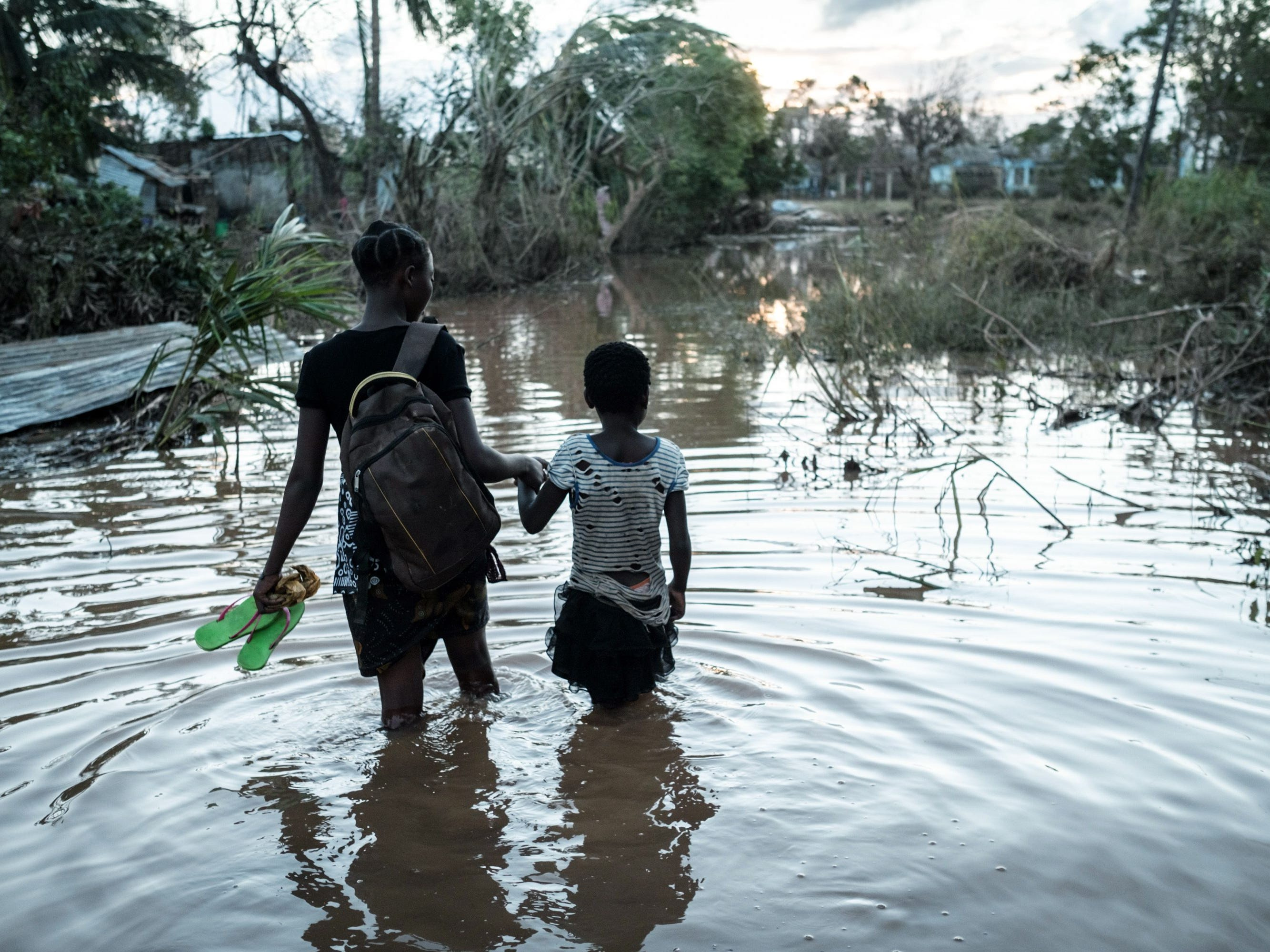 Rosita Moises Zacarias, left, 15, holding the hand of her sister Joaninha Manuel, 9, walks in flooded waters from their house destroyed by the cyclone Idai, to go to seep in a shelter in Buzi, Mozambique, on March 22, 2019.
