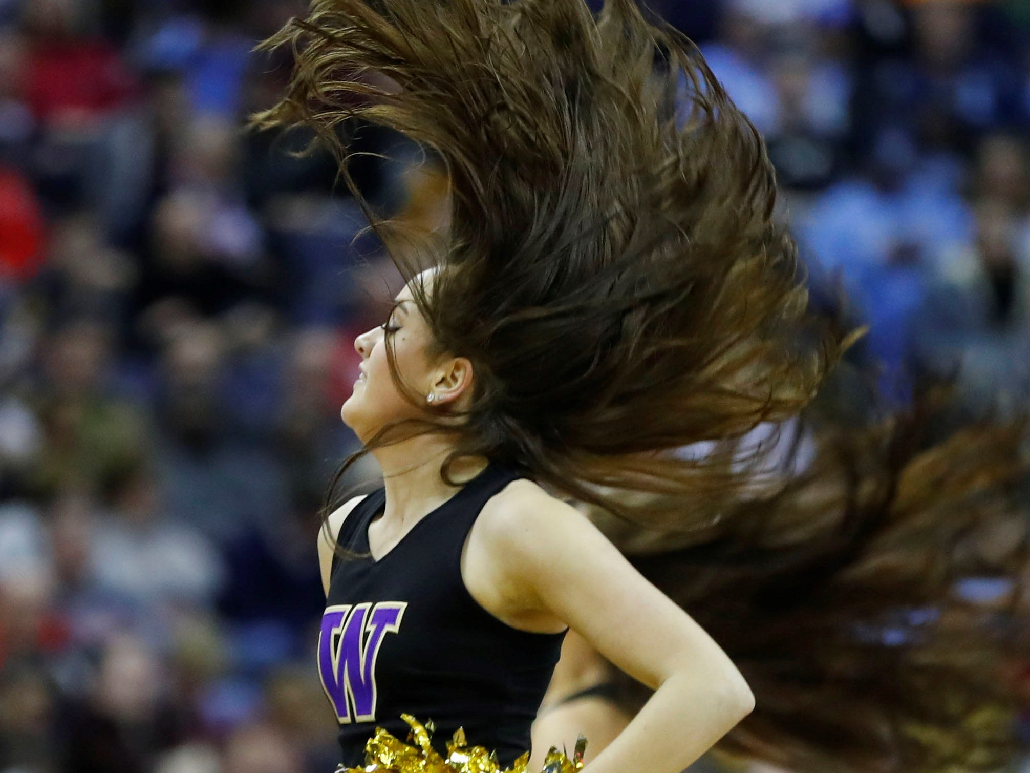 First round: A Washington Huskies cheerleader performs during the game against the Utah State Aggies.