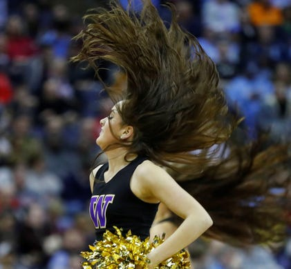 First round: A Washington Huskies cheerleader performs during a game against the Utah State Aggies.