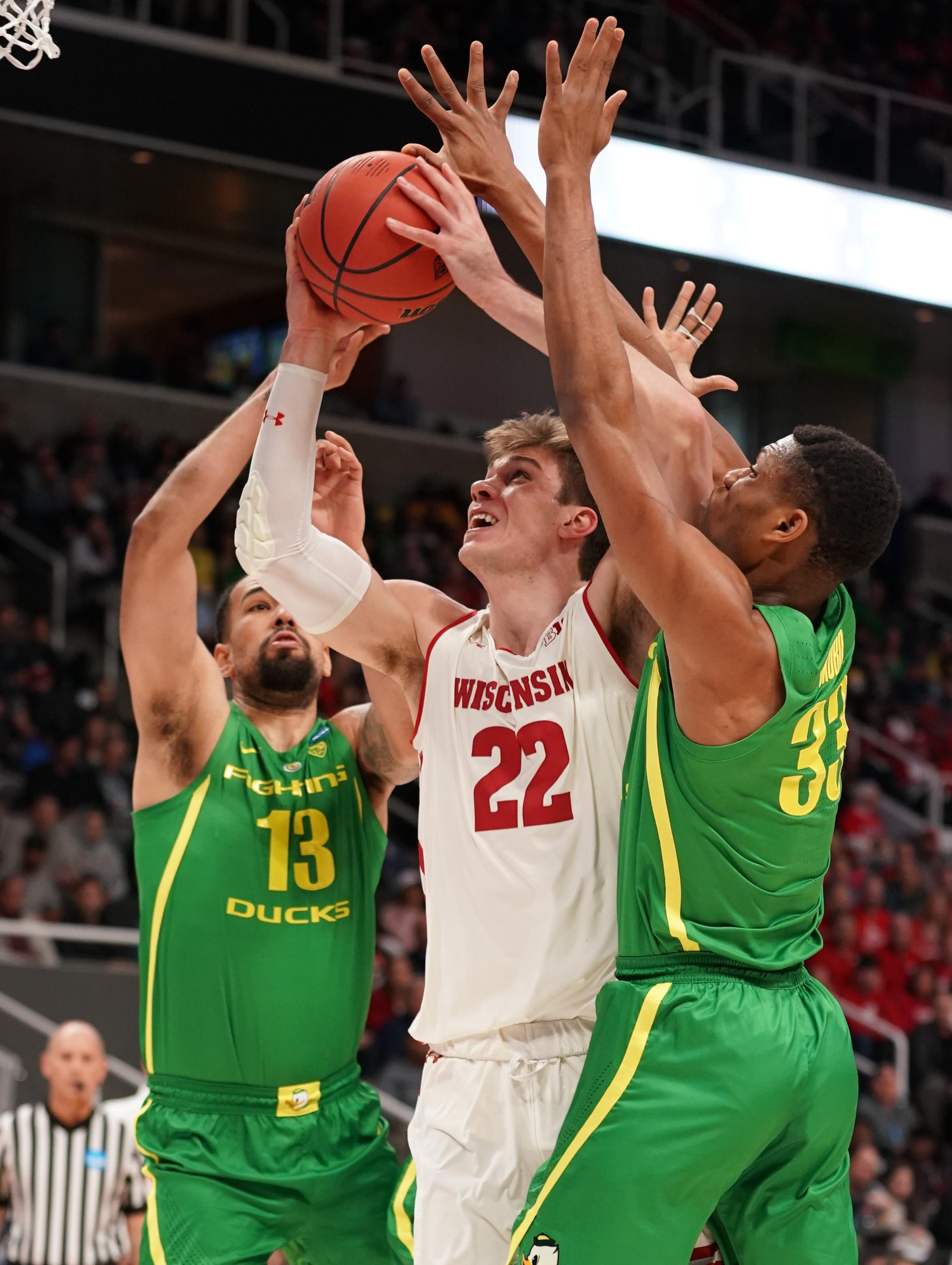 Wisconsin forward Ethan Happ tries to get a shot off while defended by Oregon's Paul White (13) and Francis Okoro (33).