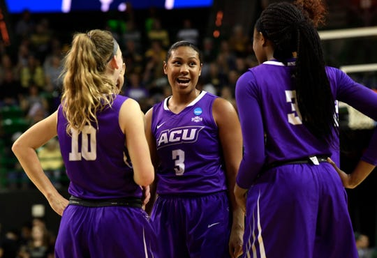 ACU forward Domique Golightly chats with teammates Breanna Wright (left) and Alyssa Adams during a timeout at Saturday's NCAA Tournament game in Waco.