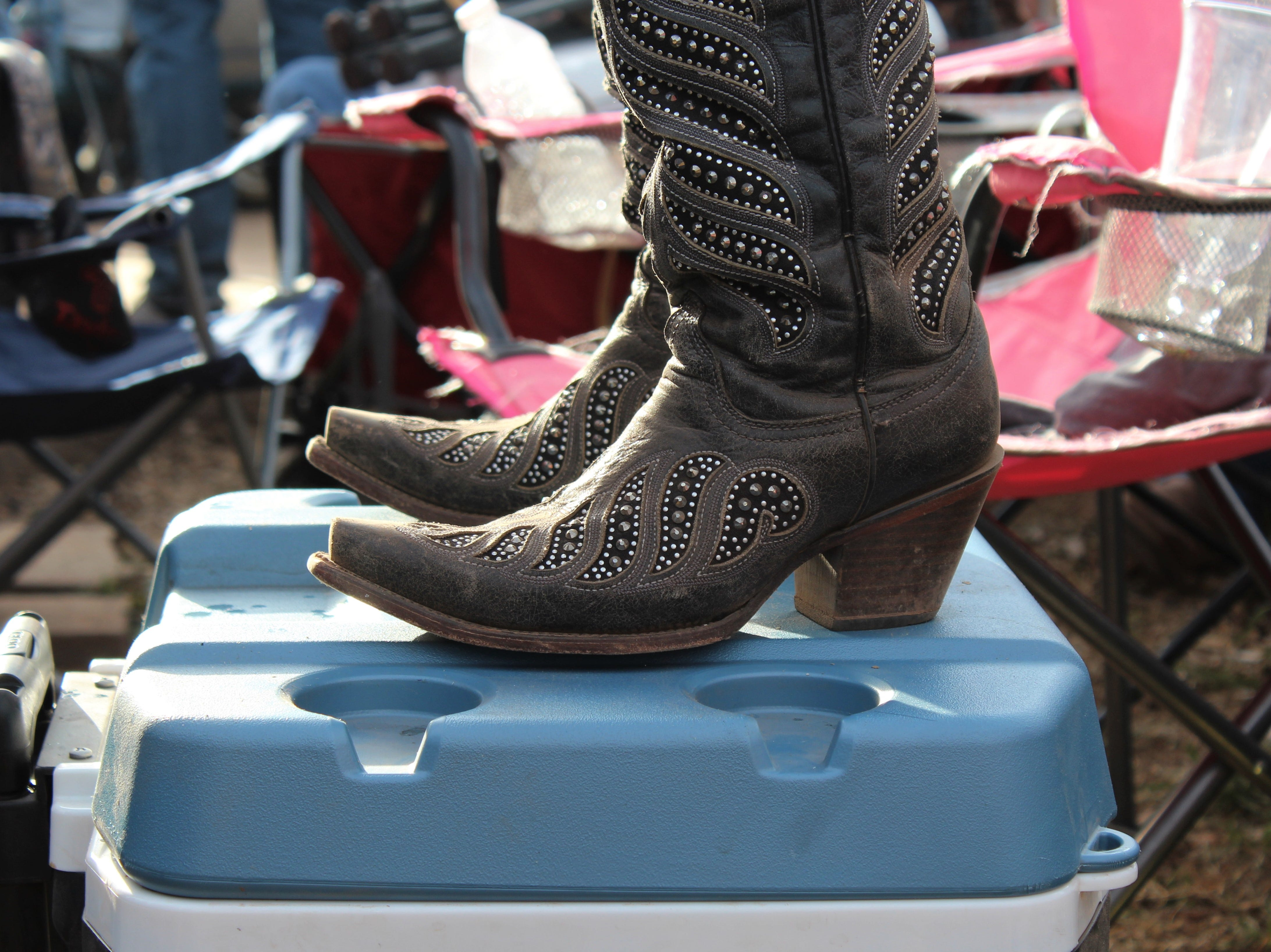 A music fan in boots gets a better look at the stage by standing on her cooler Saturday afternoon March 23, 2019, at the 9th Outlaws & Legends Music Festival.