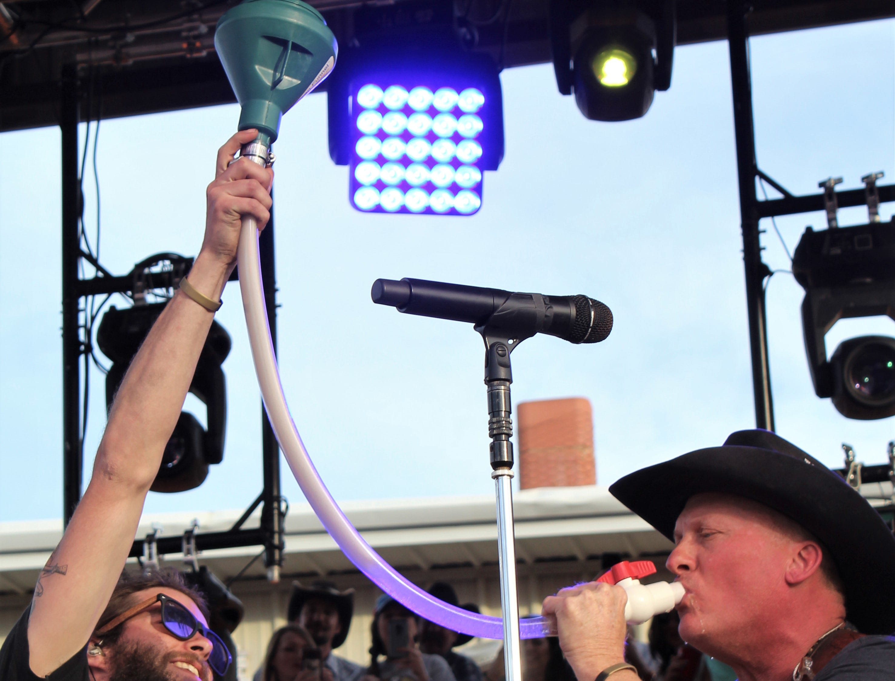 "Kevin Fowler, right, is the fast-track recipient of a Coors Light during his set Saturday afternoon March 23, 2019, at the Outlaws & Legends Music Festival. Fowler had mentioned no one lets him partake of a ""beer bong,"" then was passed the device from the crowd."