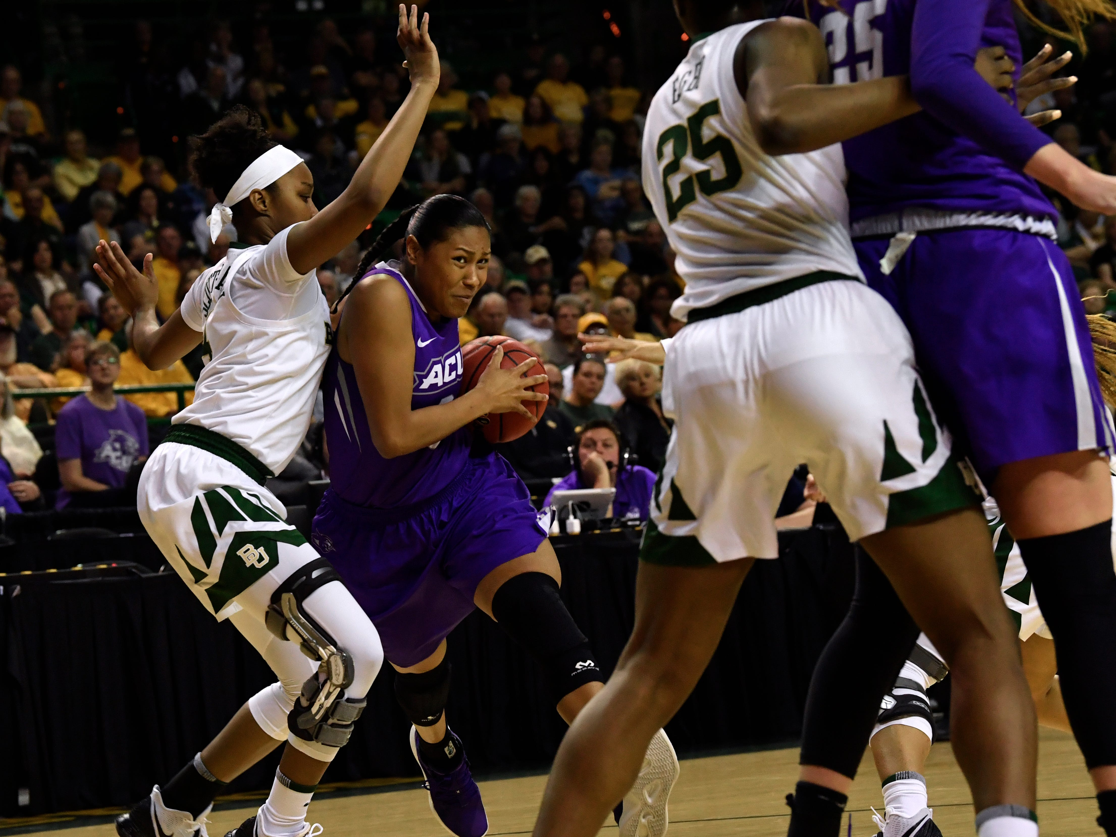 ACU forward Dominque Golightly drives for the paint past Baylor's Honesty Scott-Grayson during Saturday's NCAA Tournament women's round 1 basketball game March 23, 2019. Baylor defeated Abilene Christian University, 95-38.