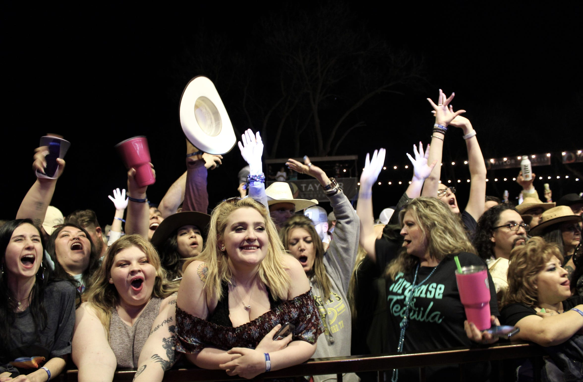 Midland fans, with women in the majority, cheer the Texas trio during the band's headlining performance March 22 at the Ninth Outlaws & Legends Music Festival. More than 12,000 attended the two-day event, a record.