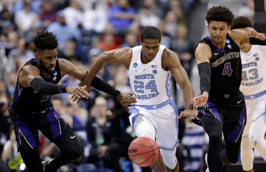 Washington's Jaylen Nowell, left to right, North Carolina's Kenny Williams and Washington's Matisse Thybulle battle for a loose ball in the first half during a second round men's college basketball game in the NCAA Tournament in Columbus, Ohio, Sunday, March 24, 2019.